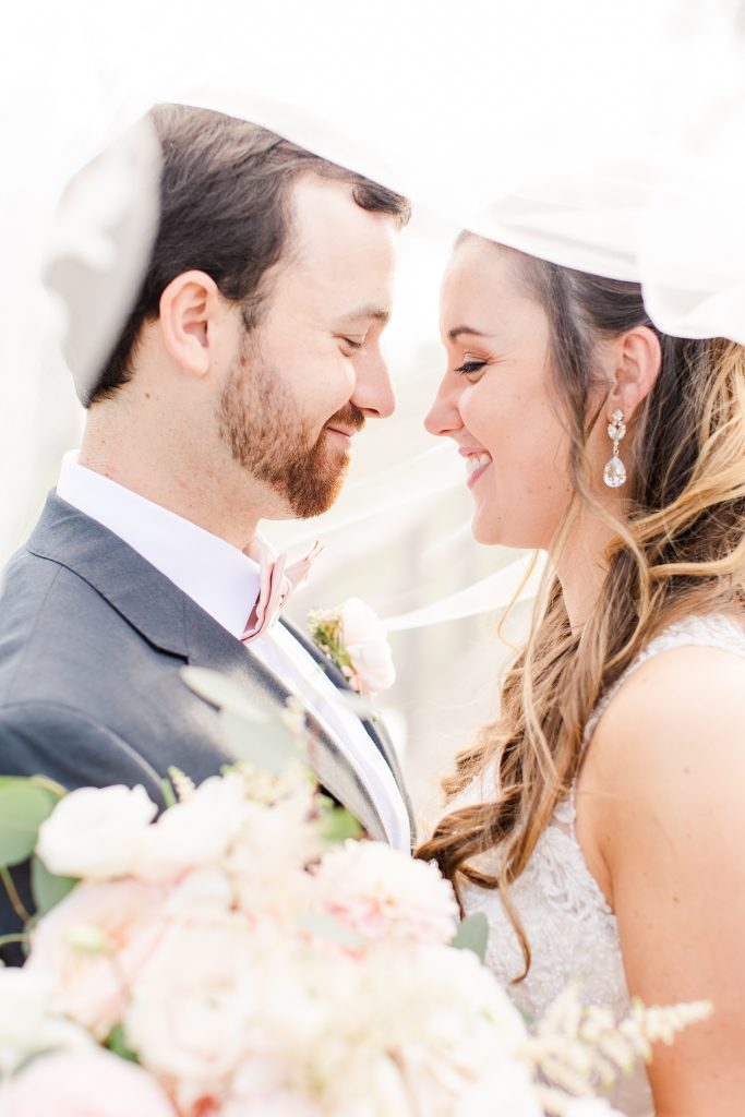 newlyweds pose under veil at Izenstone