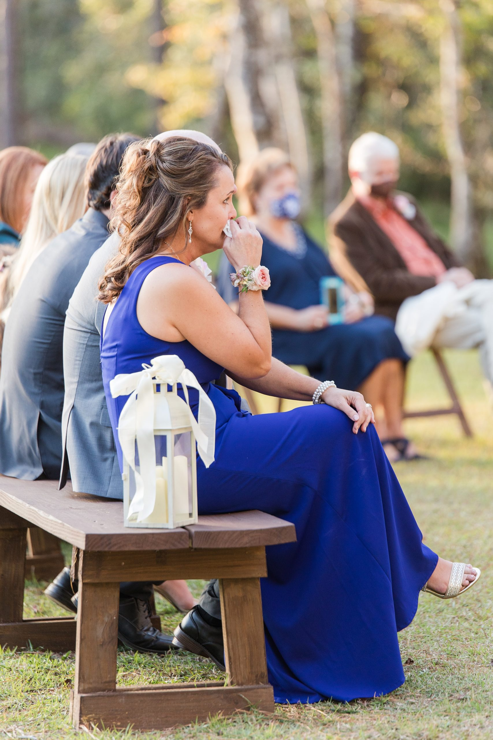 parents sit on bench during elegant outdoor wedding ceremony in Spanish Fort AL