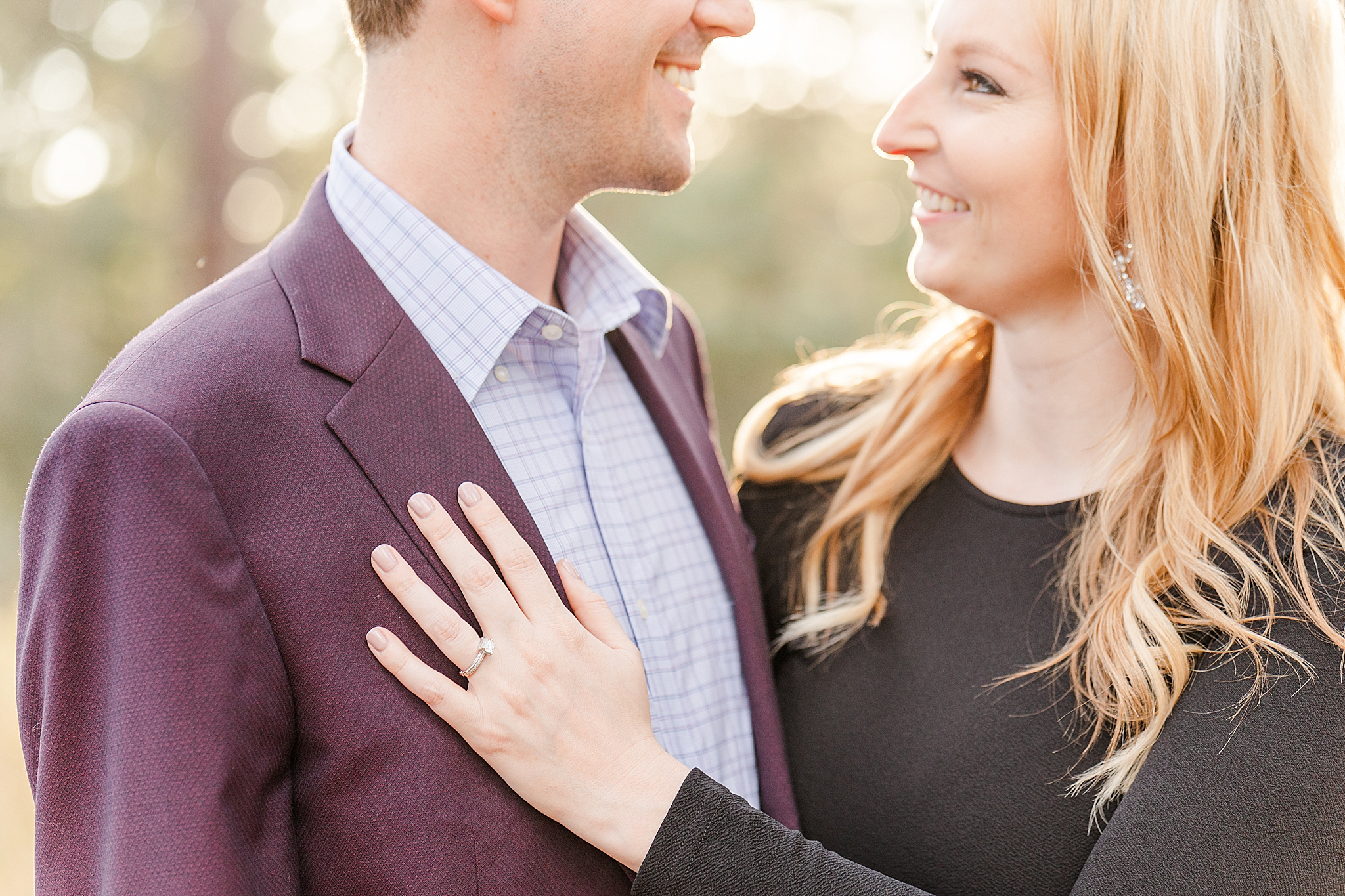 bride shows off ring on groom's chest during Mobile engagement session