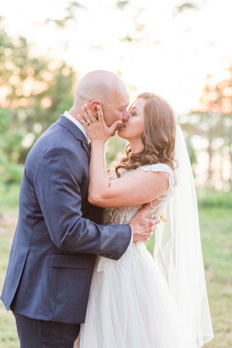 bride and groom kiss during wedding portraits in Fairhope