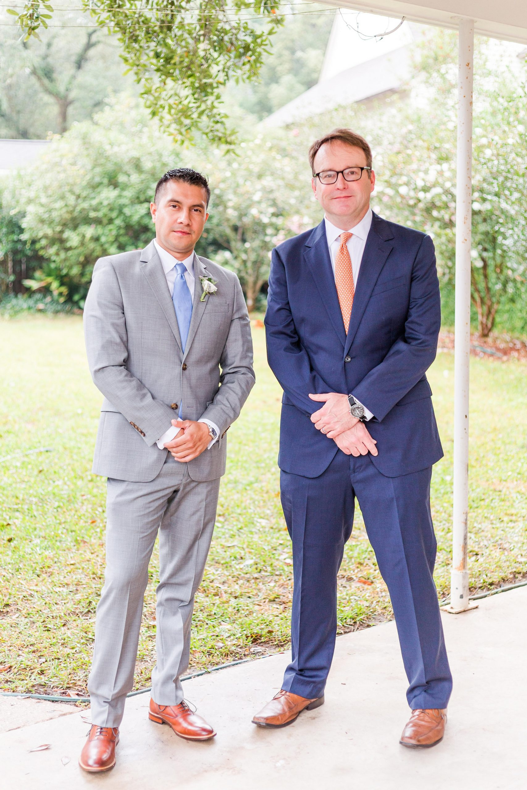 groom poses with family during wedding day prep