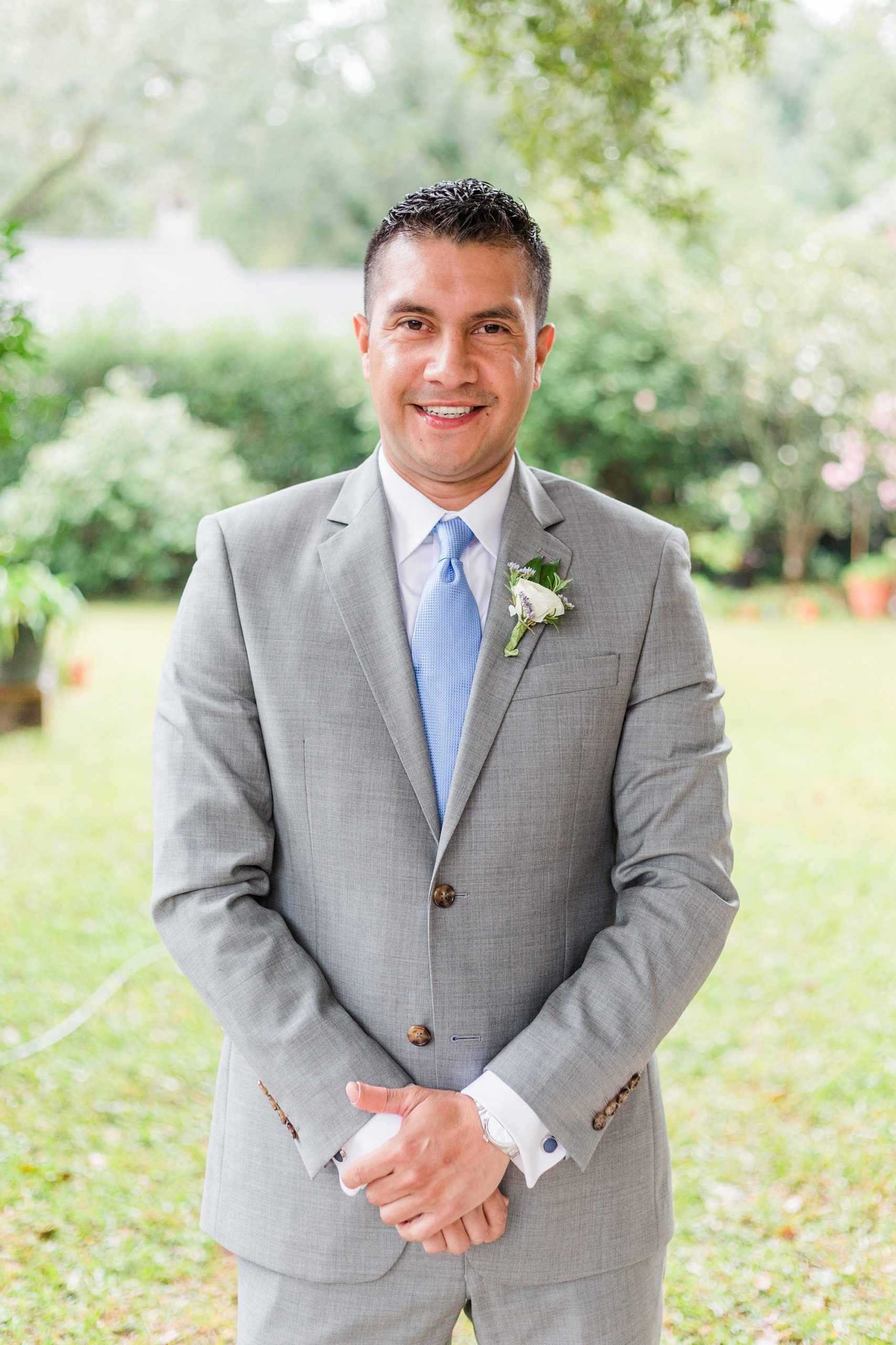 groom in grey suit poses before intimate Springhill wedding