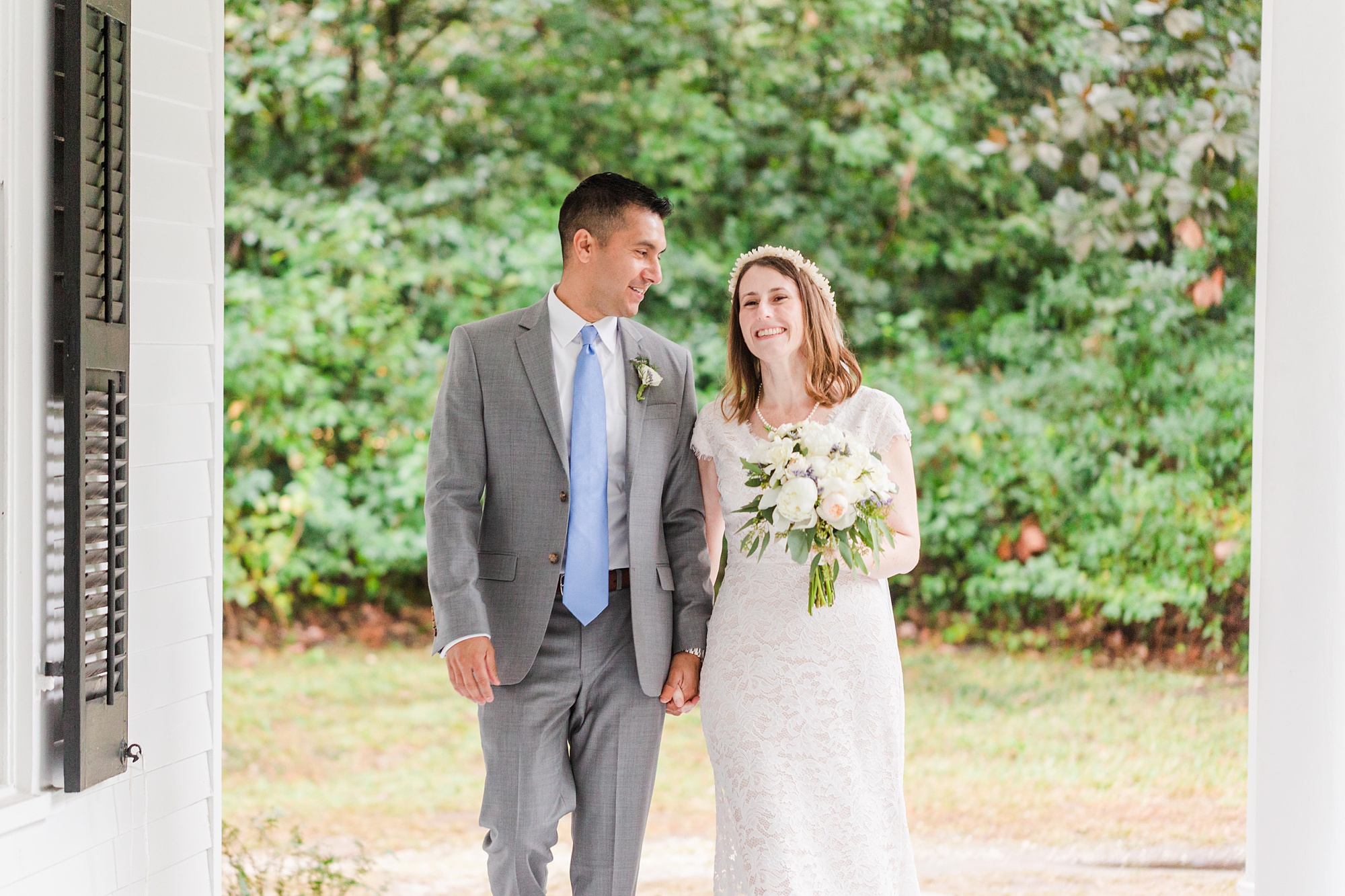newlyweds walk on front porch during intimate Springhill wedding day