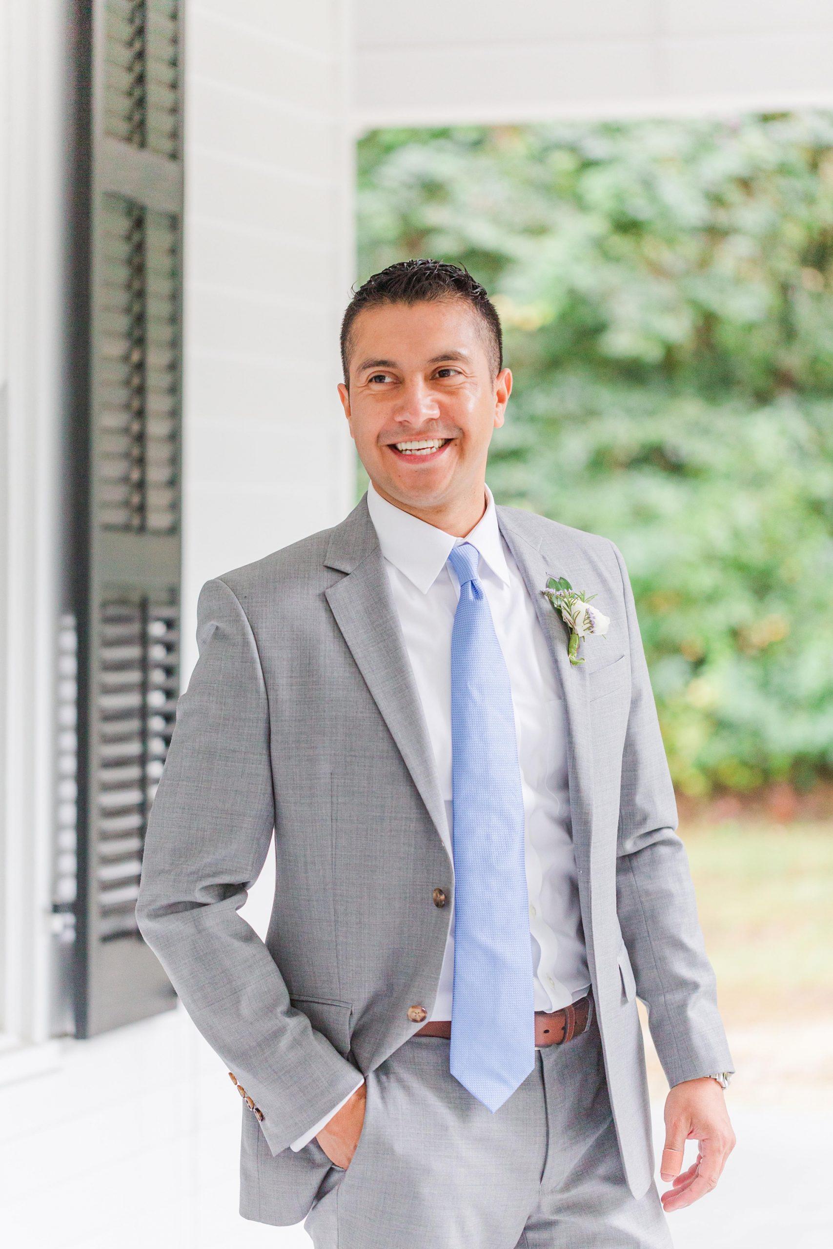 groom poses by front door in grey suit