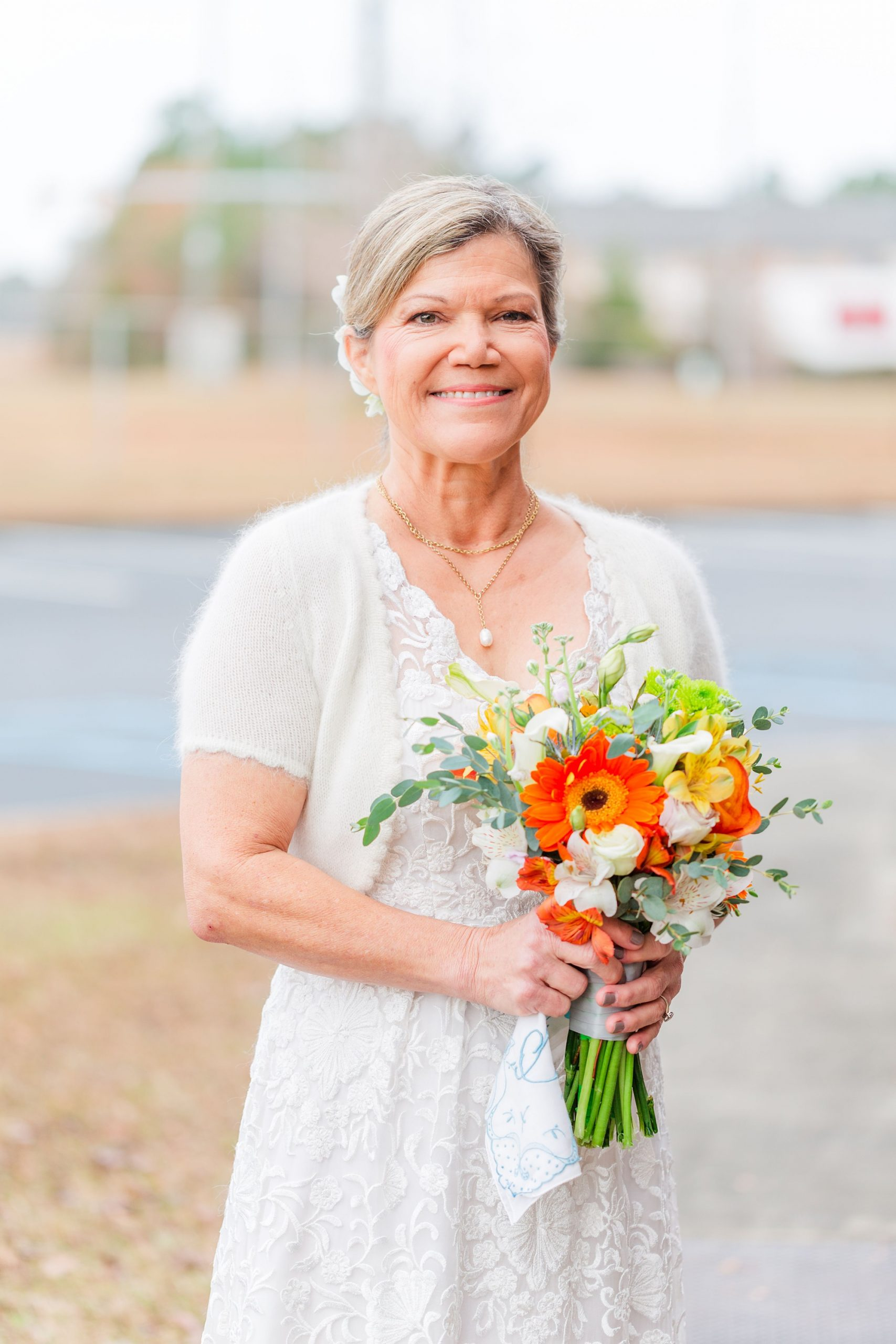 bride in white dress with sweater holds bouquet of bright wildflowers