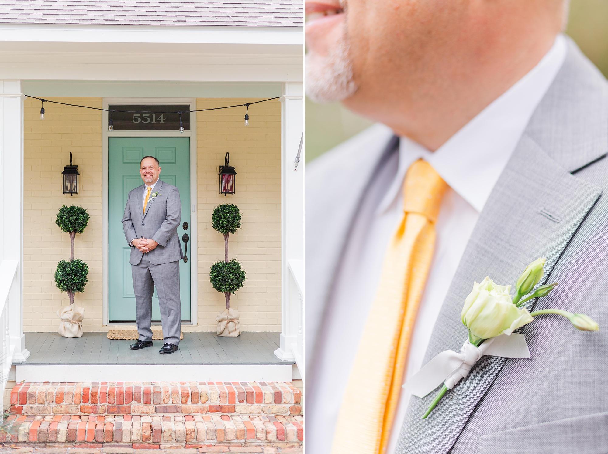 groom in grey suit with yellow tie poses in front of teal front door in Mobile AL