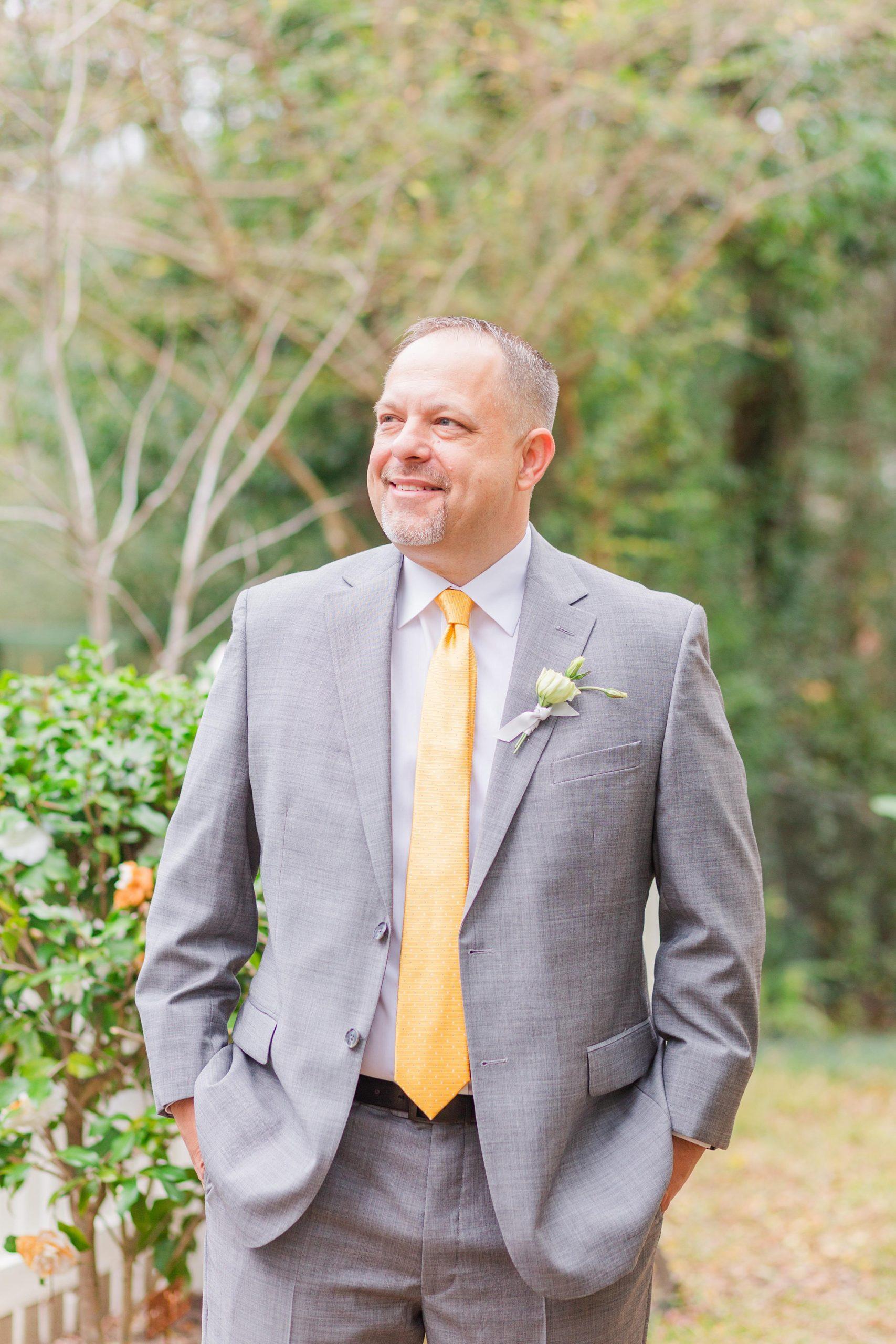 groom in grey suit with yellow tie