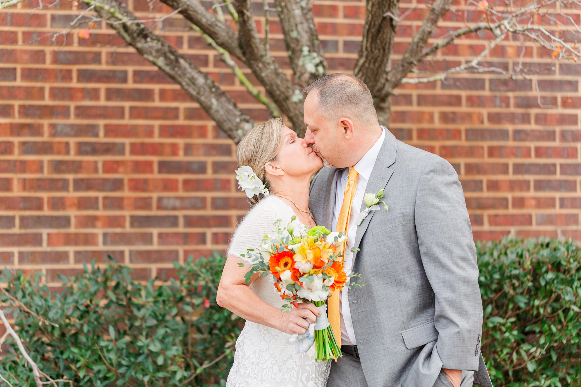 newlyweds kiss by brick building in Mobile AL