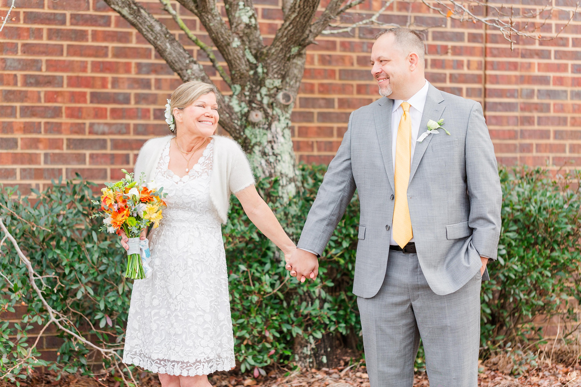bride and groom hold hands smiling at each other before AL wedding