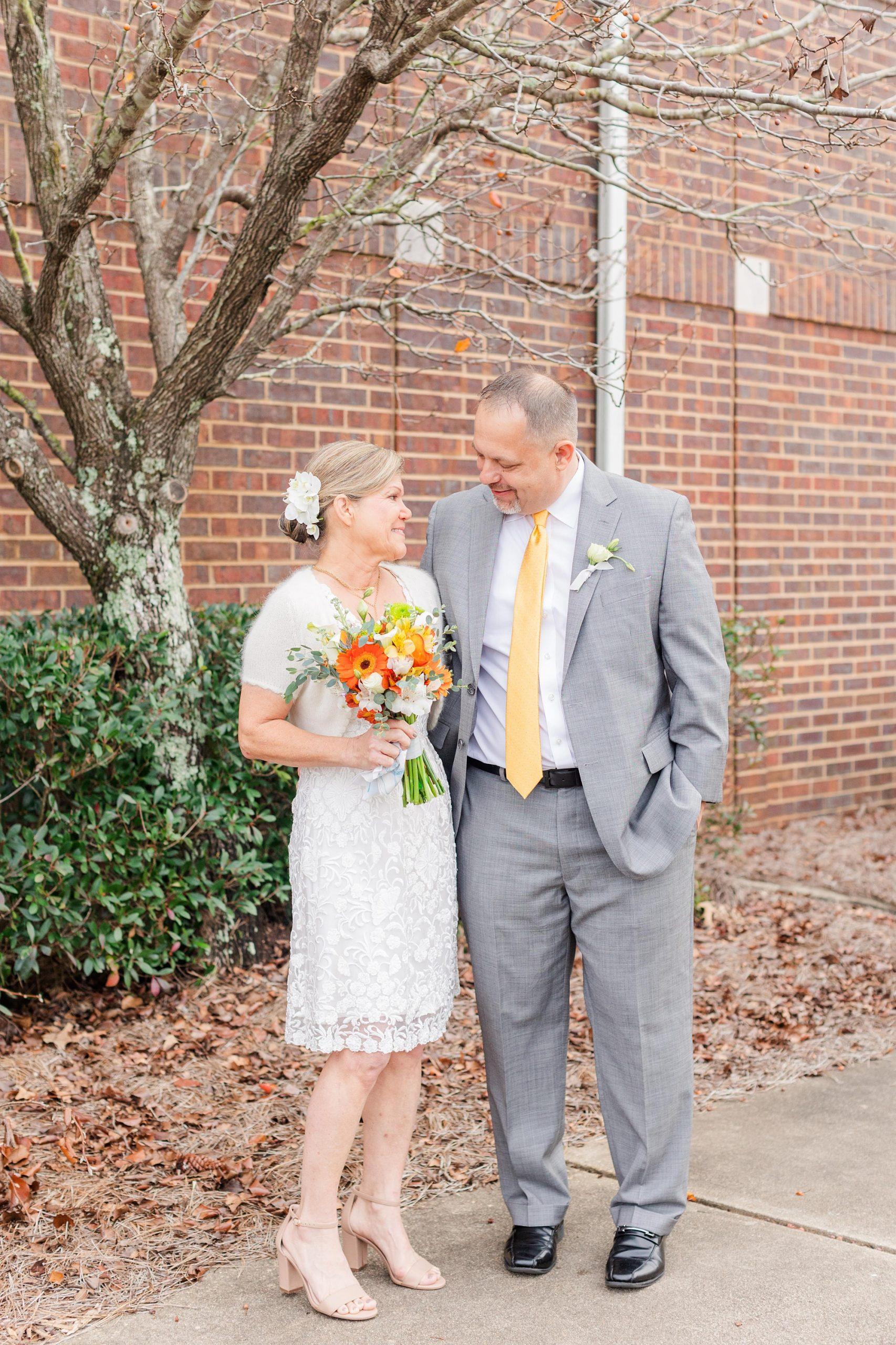 bride and groom pose together on sidewalk in Mobile AL