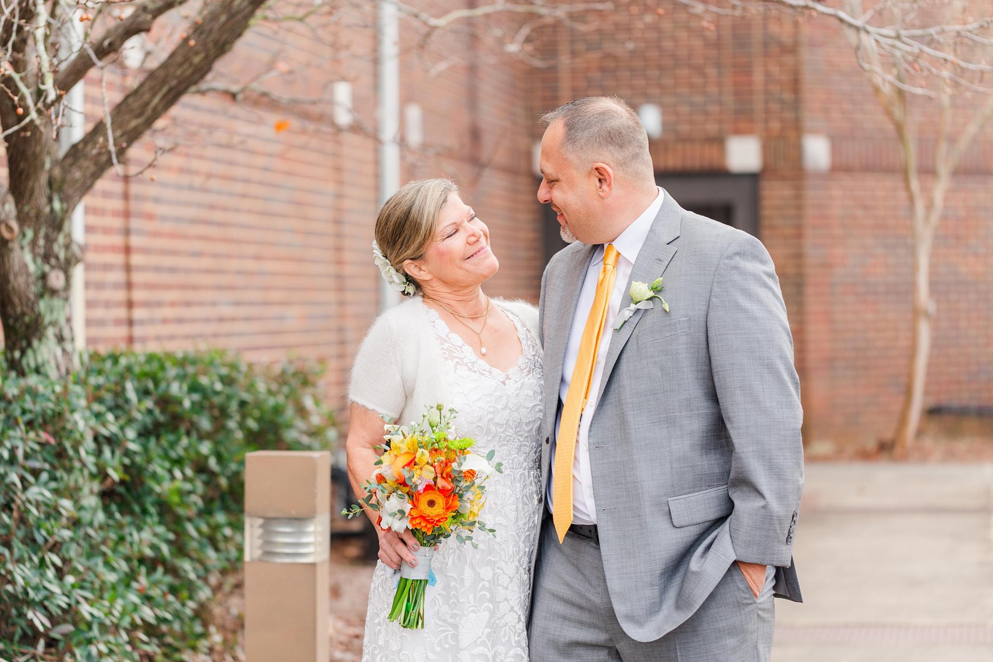 newlyweds hug on sidewalk in Mobile Alabama