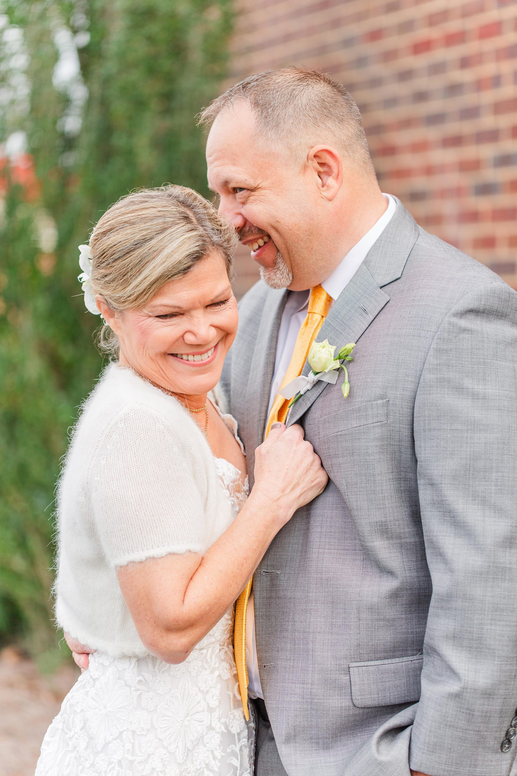 groom makes bride laugh while nuzzling forehead