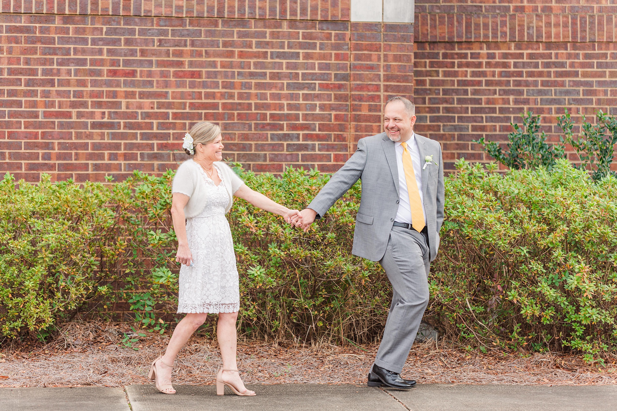bride and groom hold hands walking by brick building