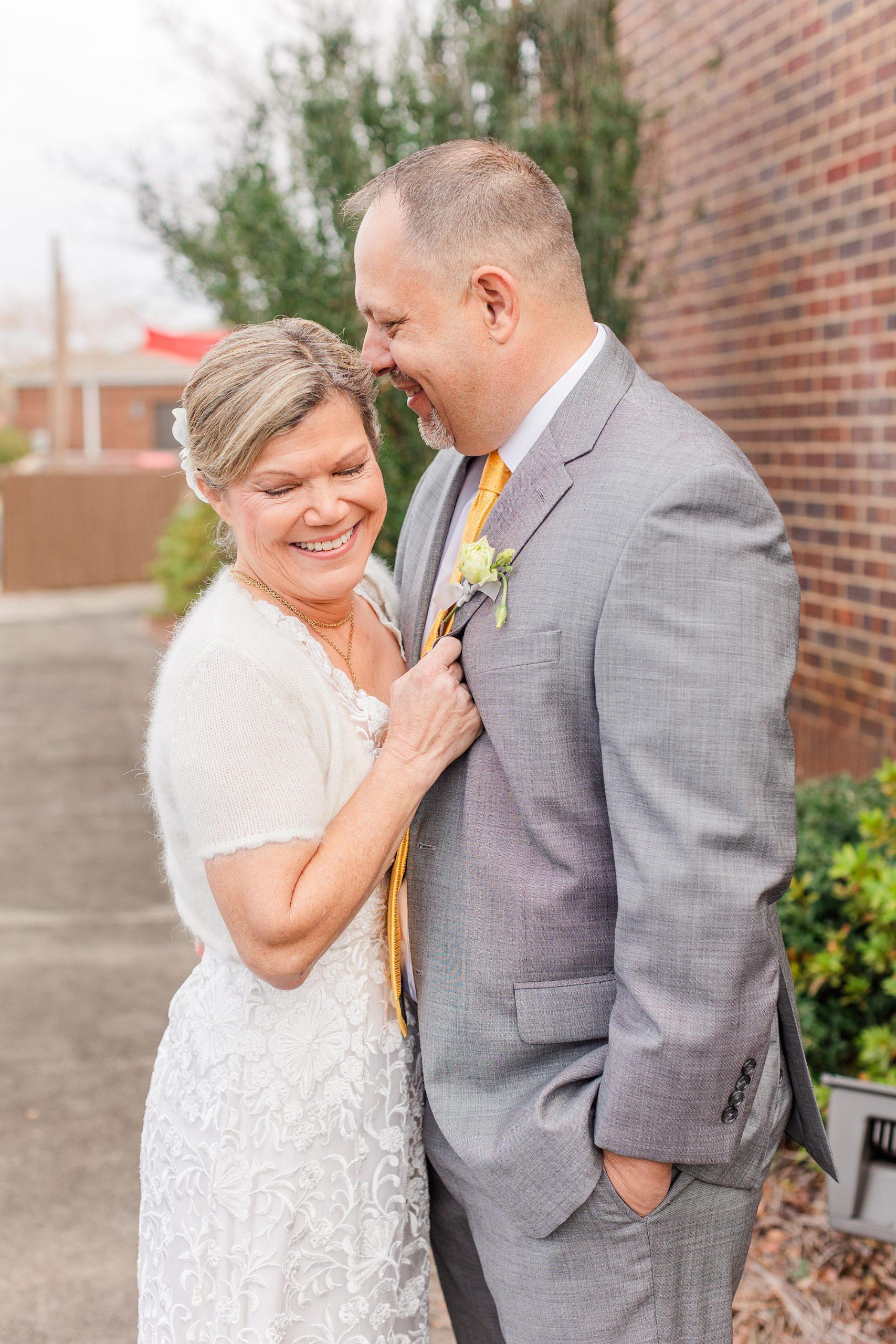 groom makes bride laugh during intimate Mobile AL wedding portraits