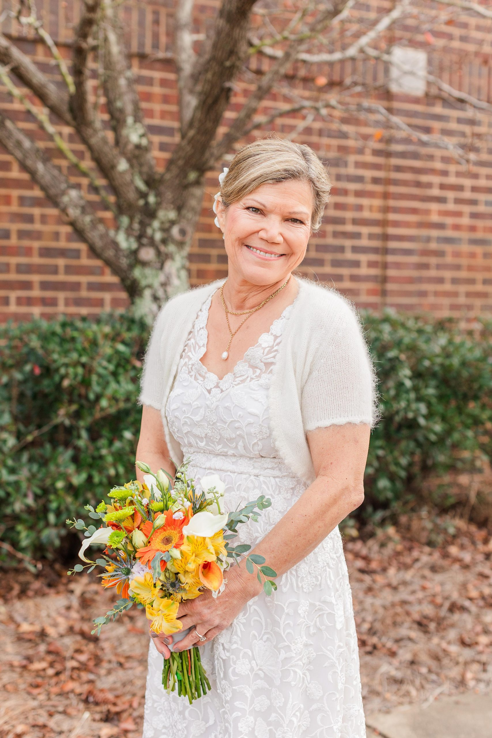 bride holds bouquet of orange and yellow wildflowers