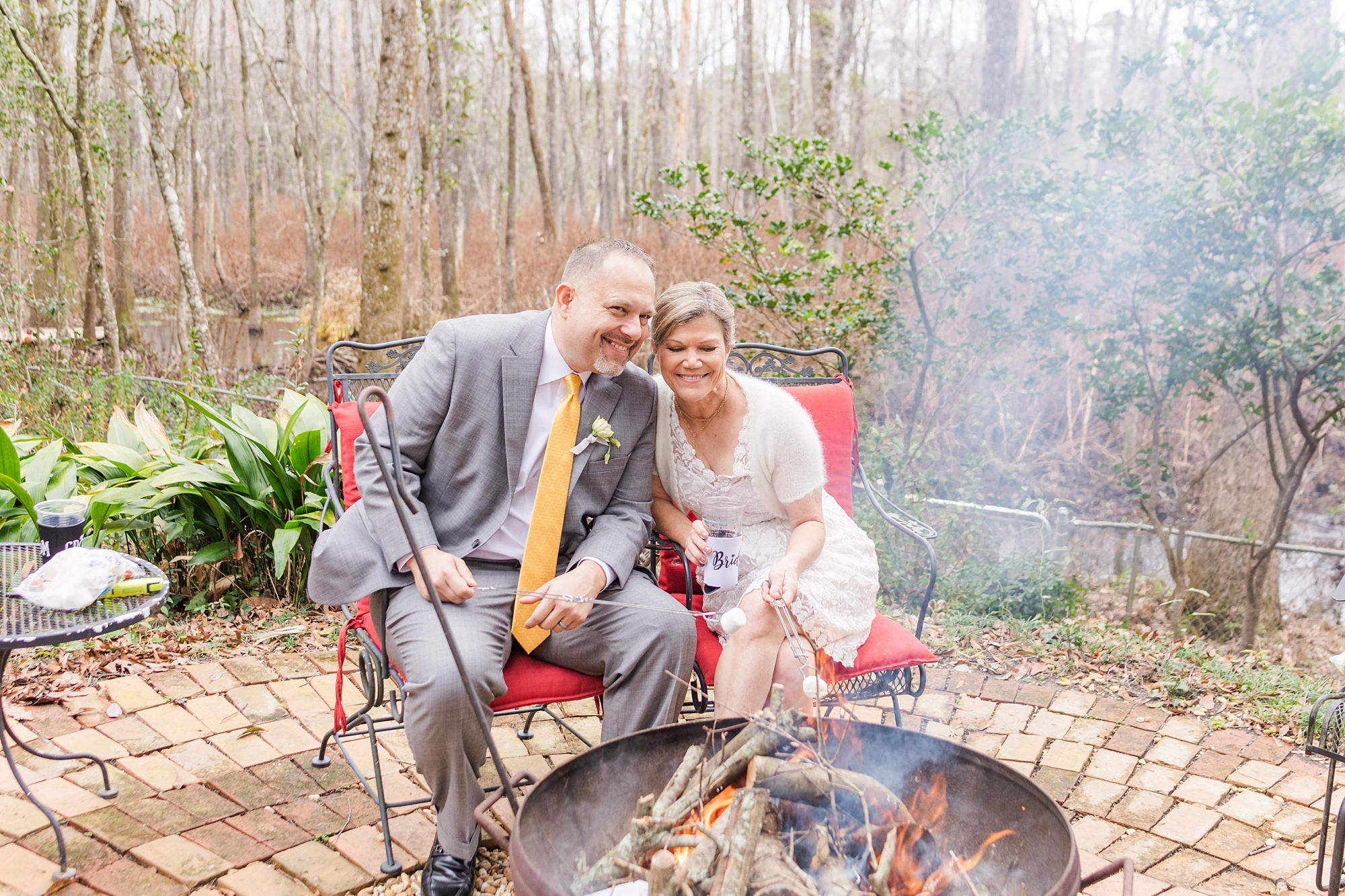 newlyweds pose by fire pit during Spring Hill backyard wedding reception