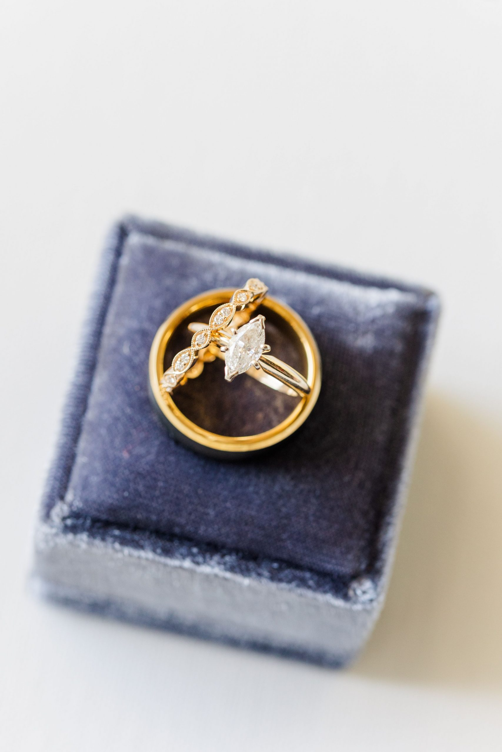 bride's wedding rings rest on pale blue ring box
