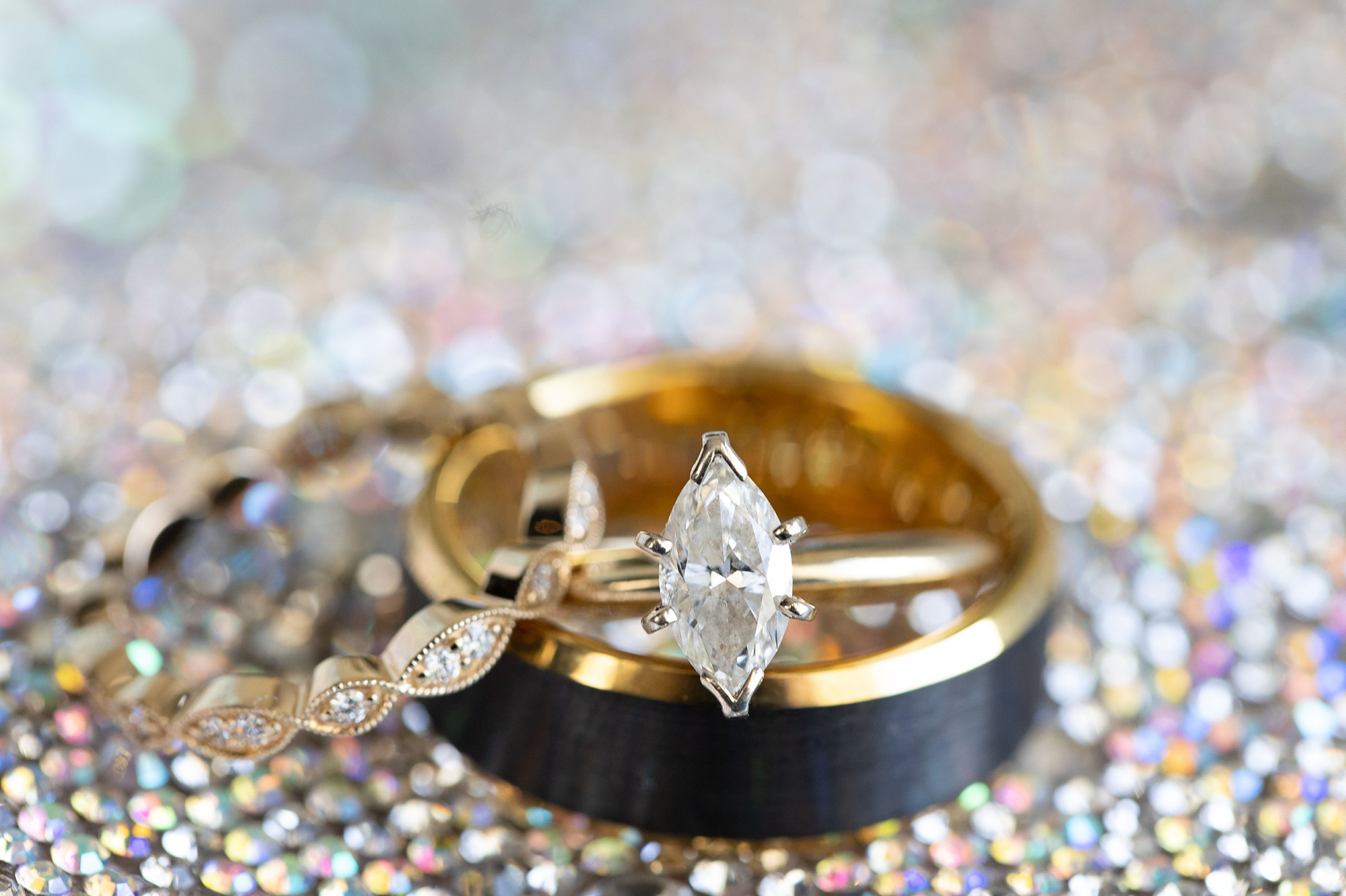 wedding bands and engagement ring sit on sparkly boots