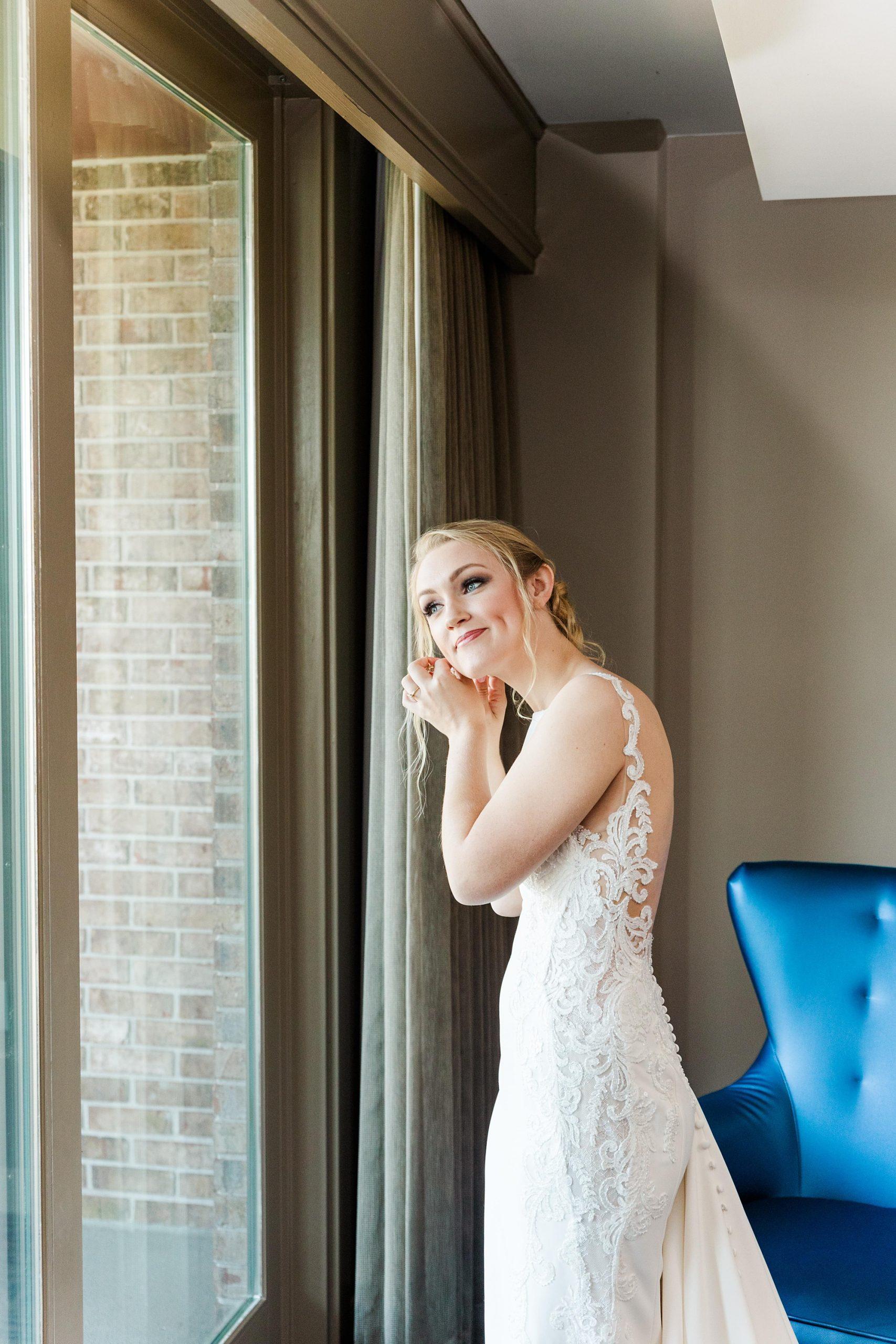 bride adjusts earrings before AL wedding