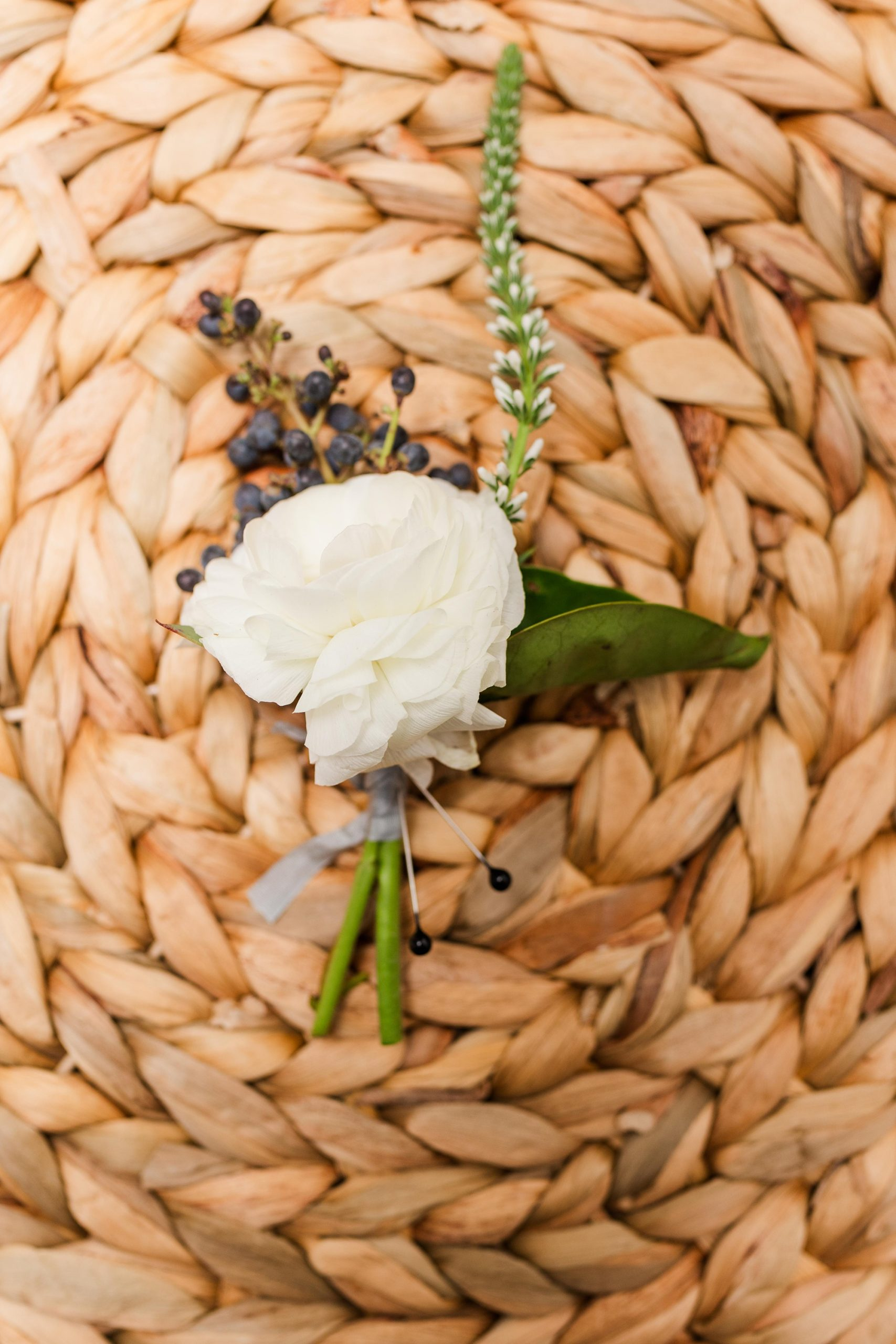 groom's boutonniere on basket before New Year's Eve wedding