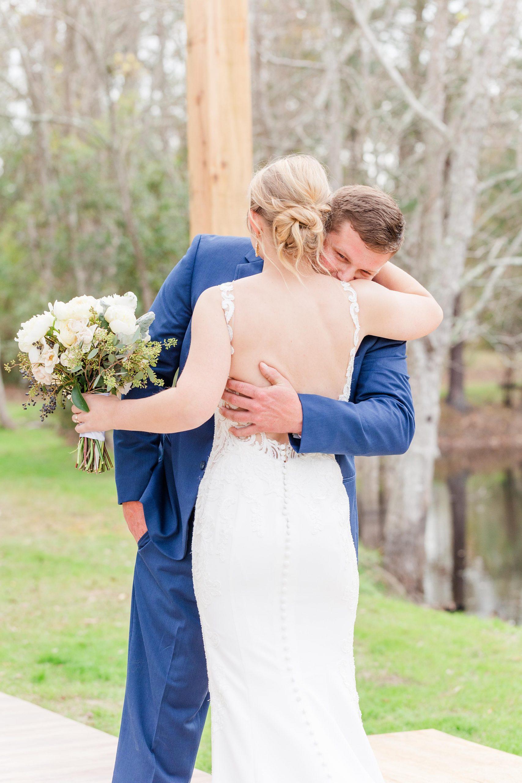 groom hugs bride during first look before New Year's Eve wedding