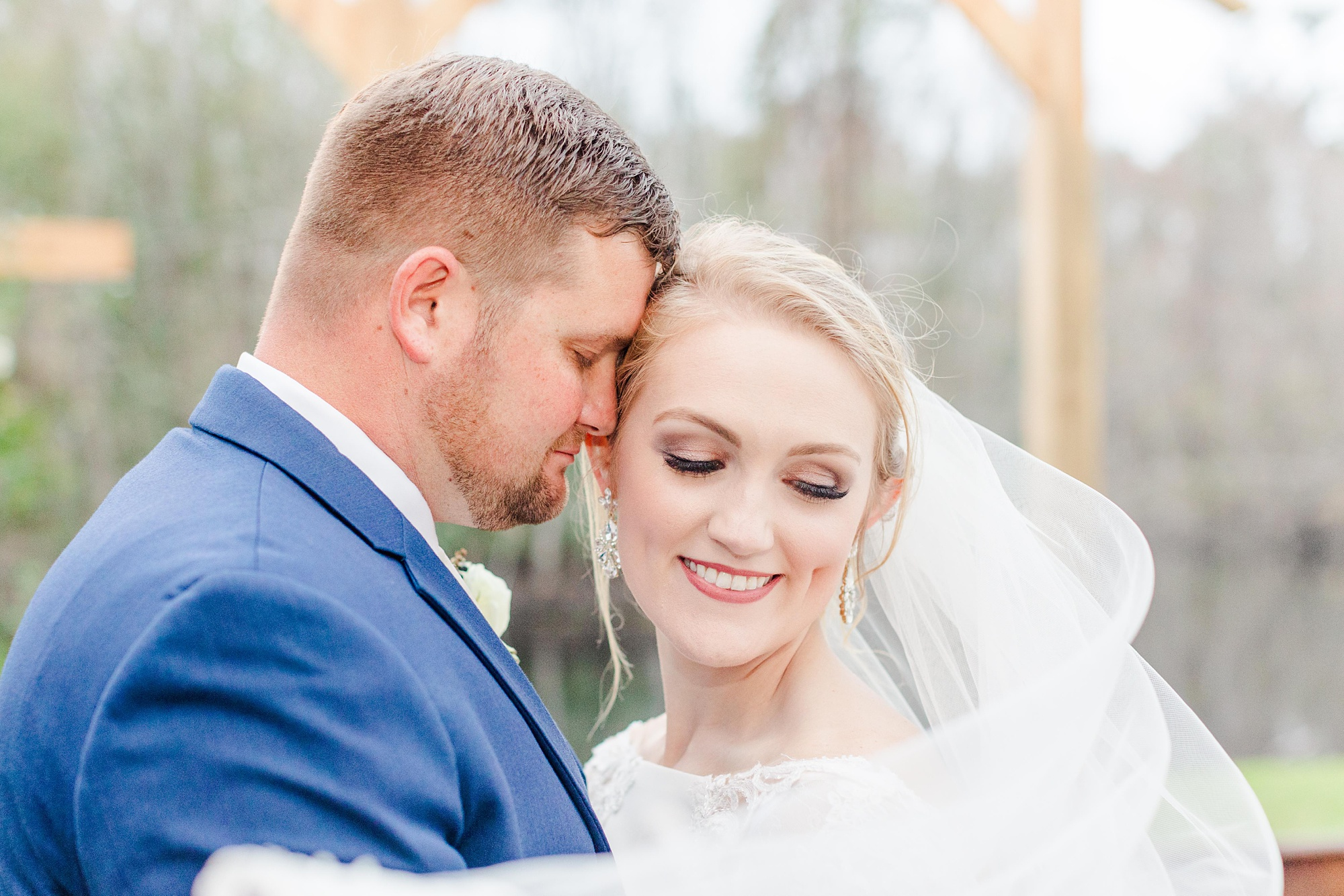 groom nuzzles bride's forehead with veil wrapped around them