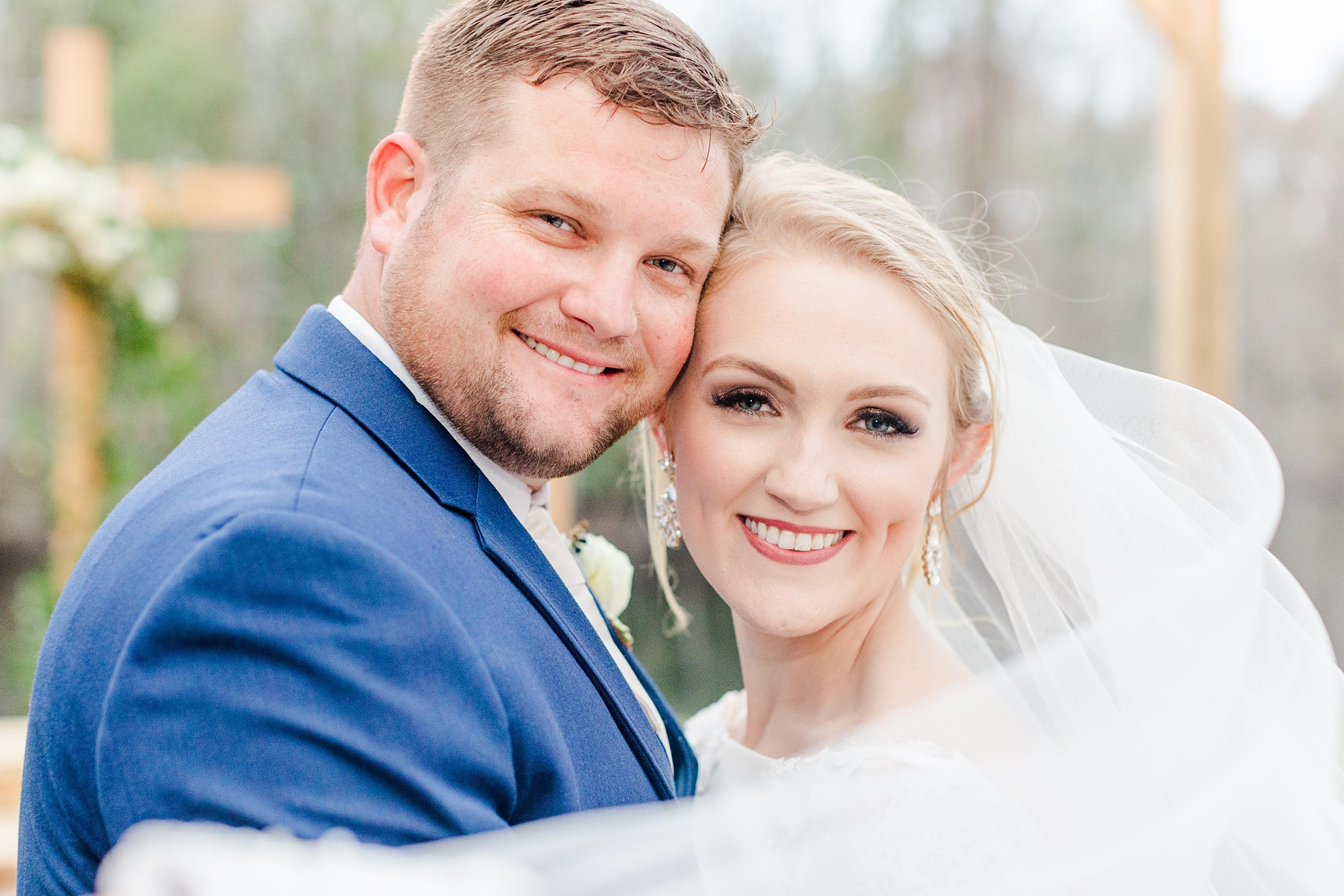 bride and groom pose with heads touching as veil floats around them