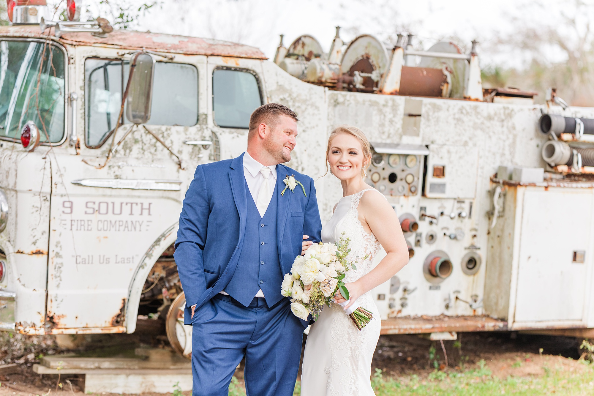bride and groom pose by old fire engine