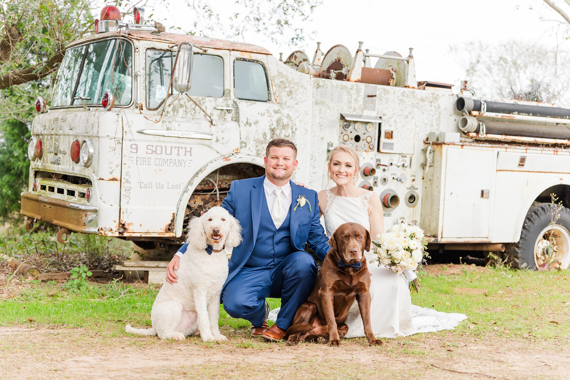 newlyweds pose with dogs in front of old fire engine