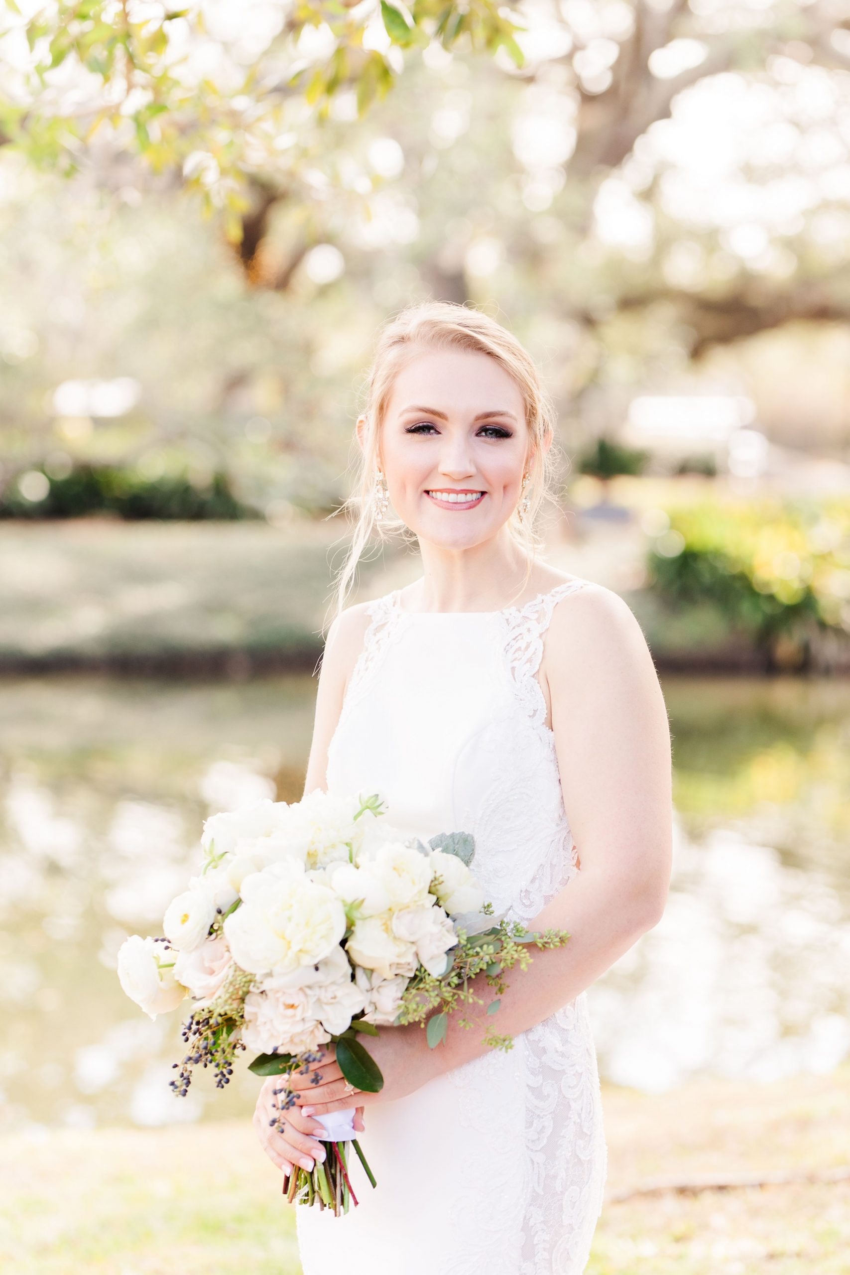 bride holds bouquet by lake at home in Magnolia Springs