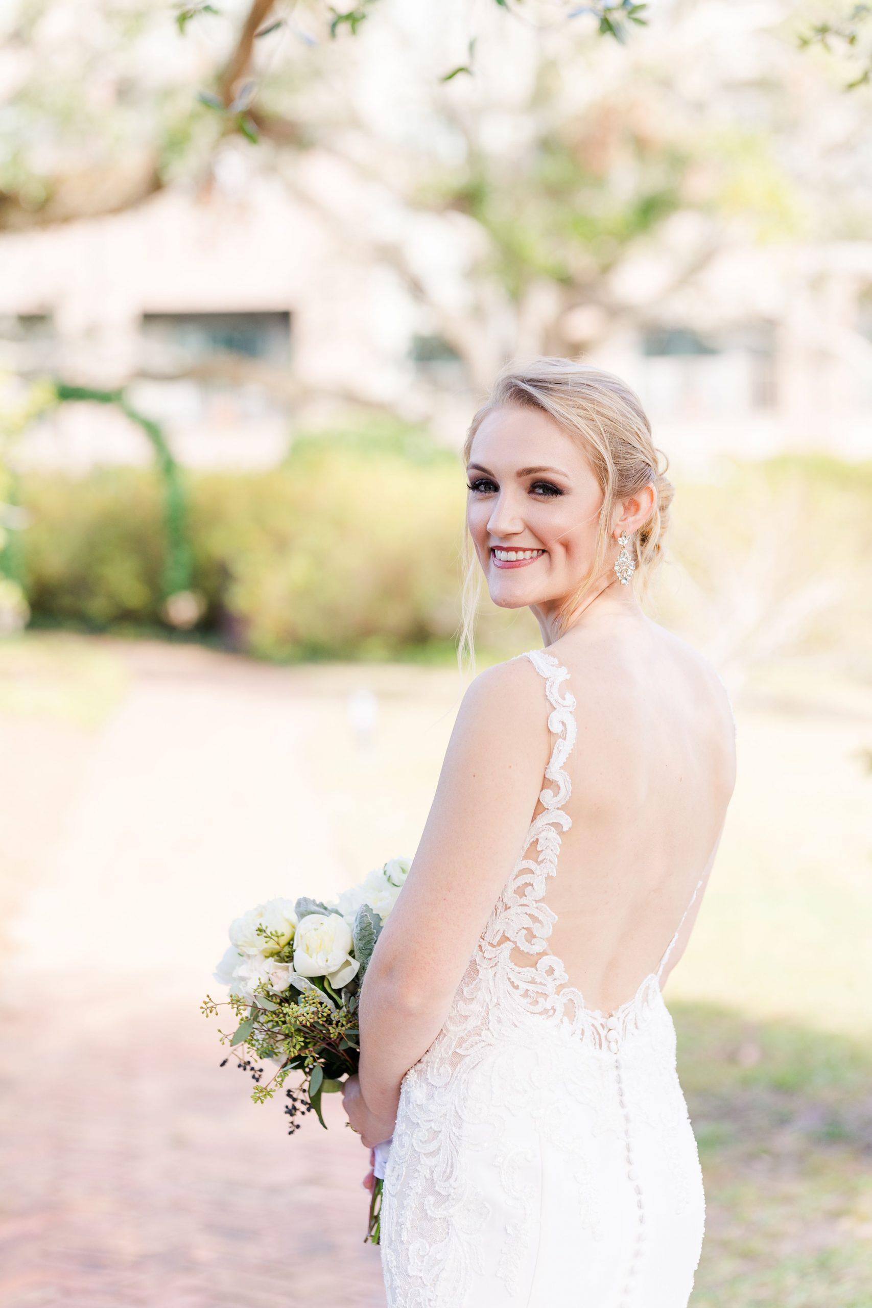 bride looks over shoulder holding bouquet