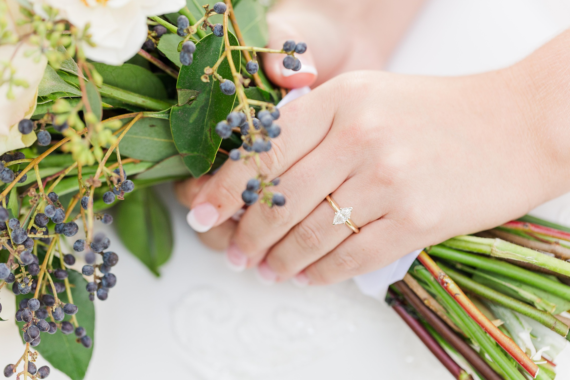 bride shows off diamond engagement ring holding bouquet