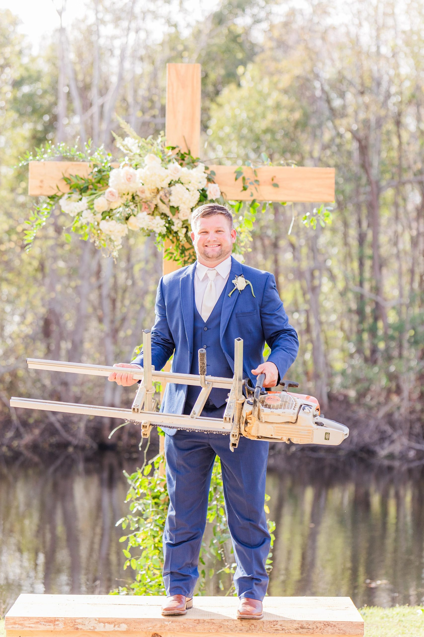 groom in blue suit holds saw