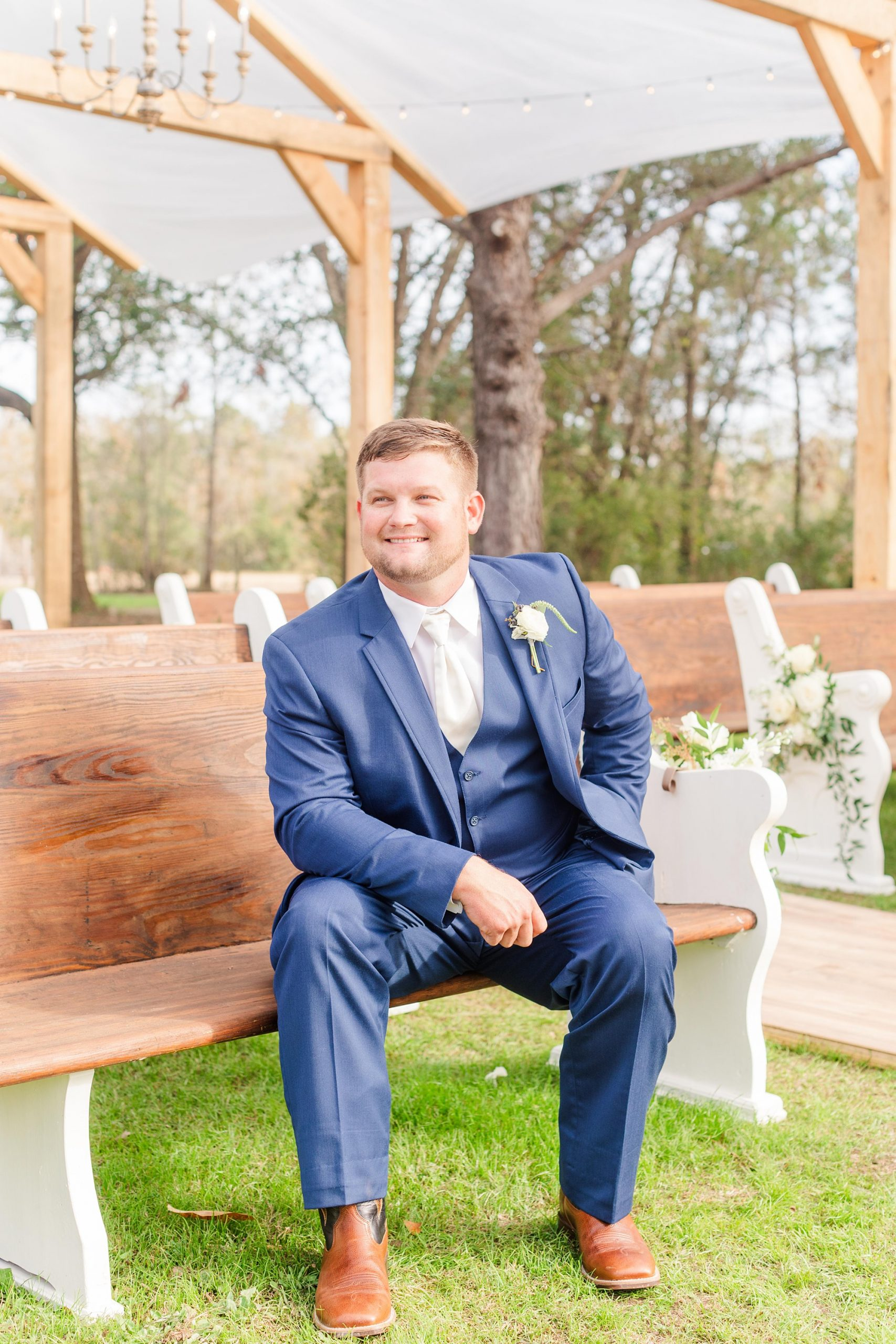 groom sits on wooden pews he built for wedding ceremony