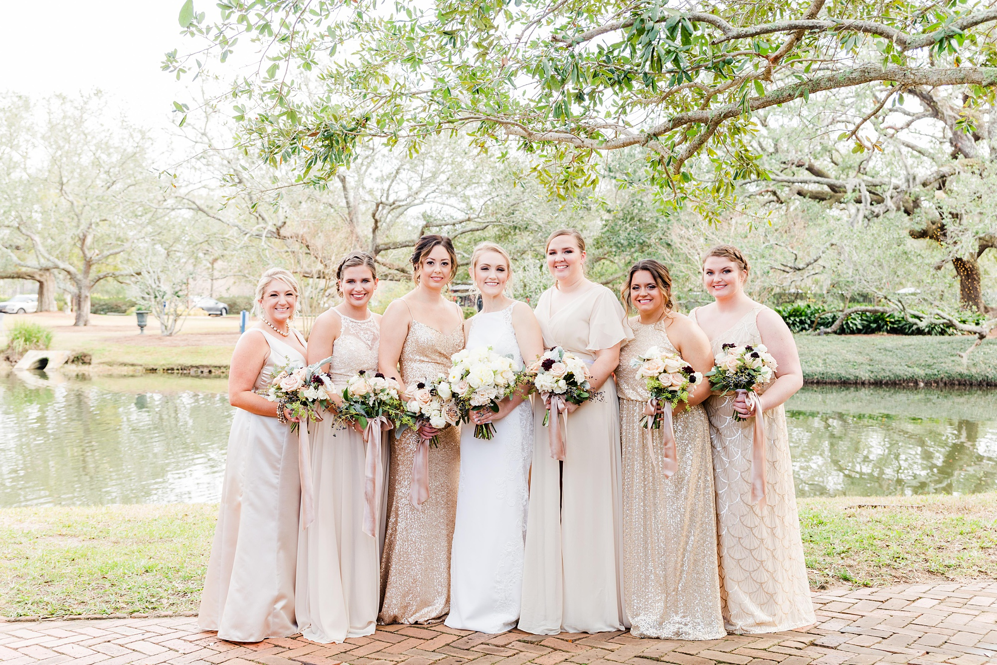 bride poses with bridesmaids in champagne gowns