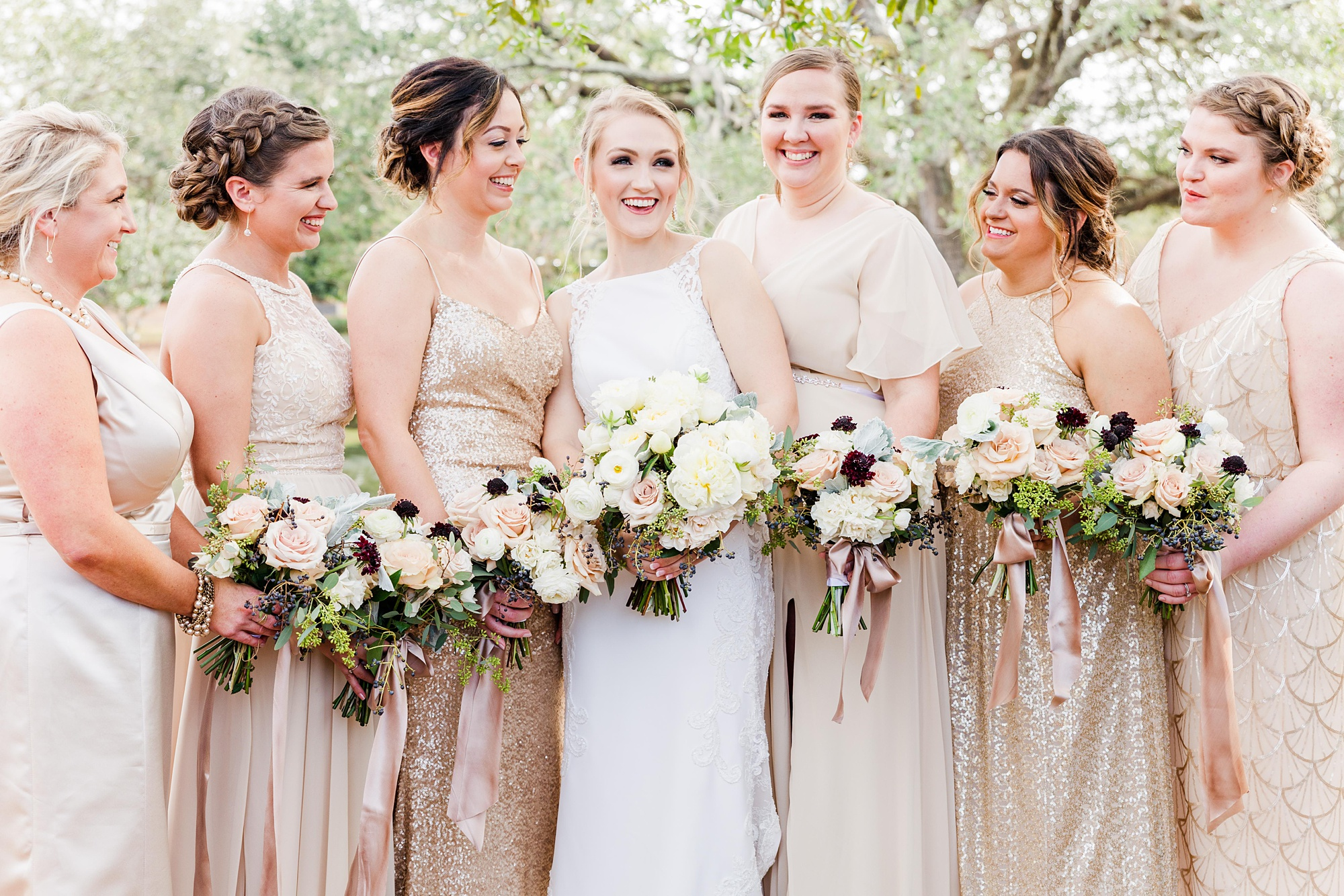 bride poses with bridesmaids in mismatched champagne gowns