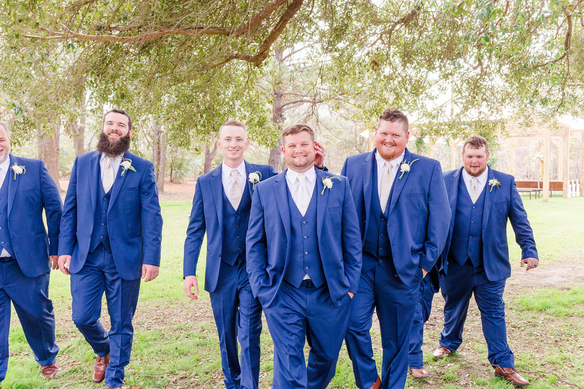 groom walks with groomsmen in blue jackets