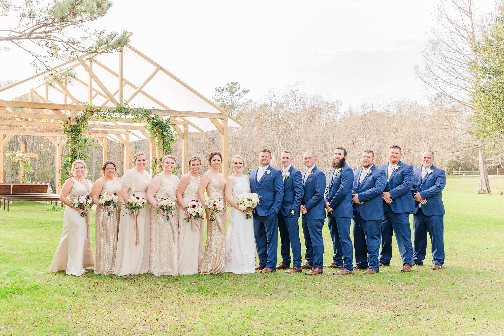 bridal party in champagne and blue poses outside wooden chapel before New Year's Eve wedding
