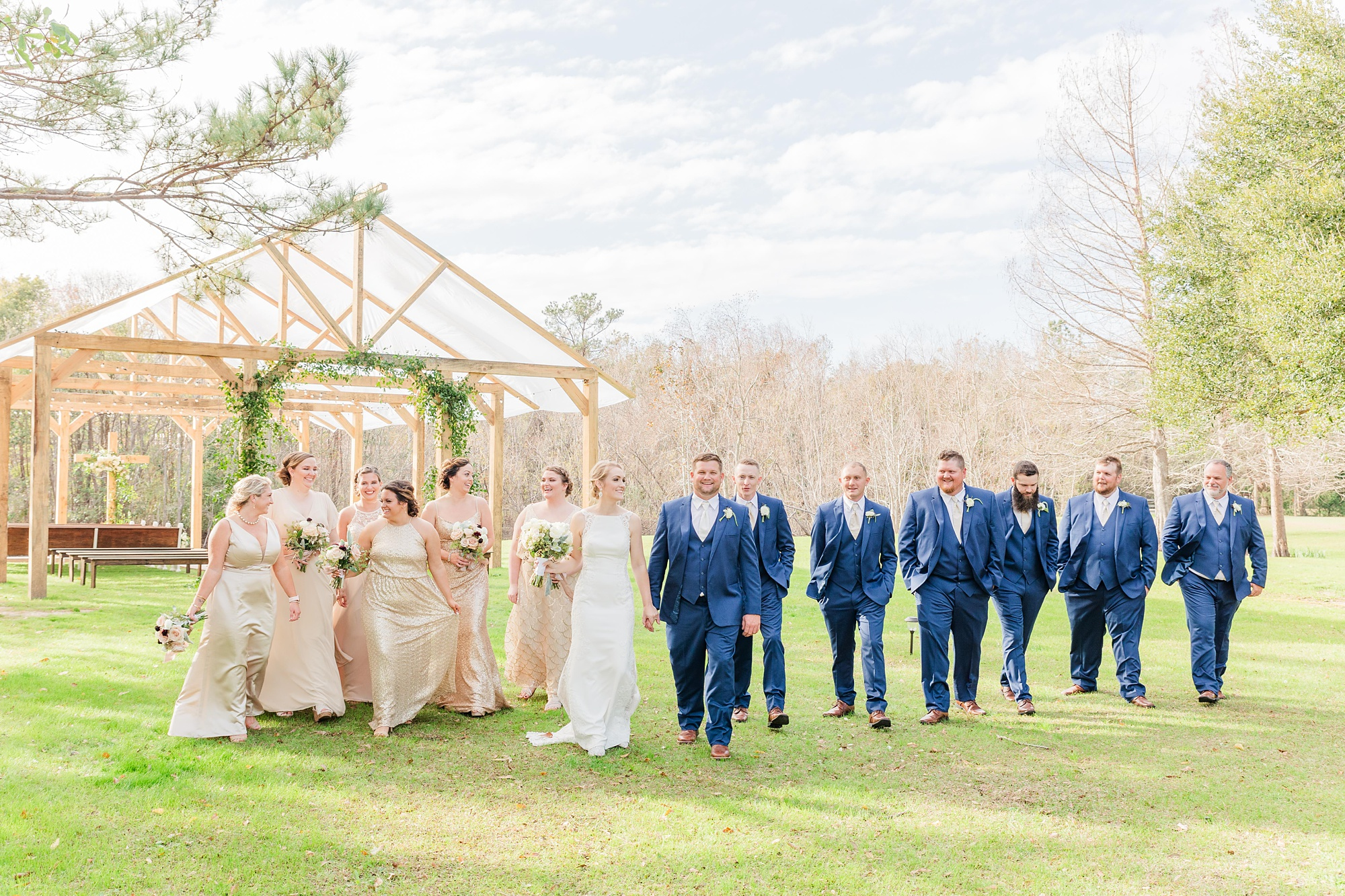 bride and groom walk with bridal party in front of wooden open air chapel