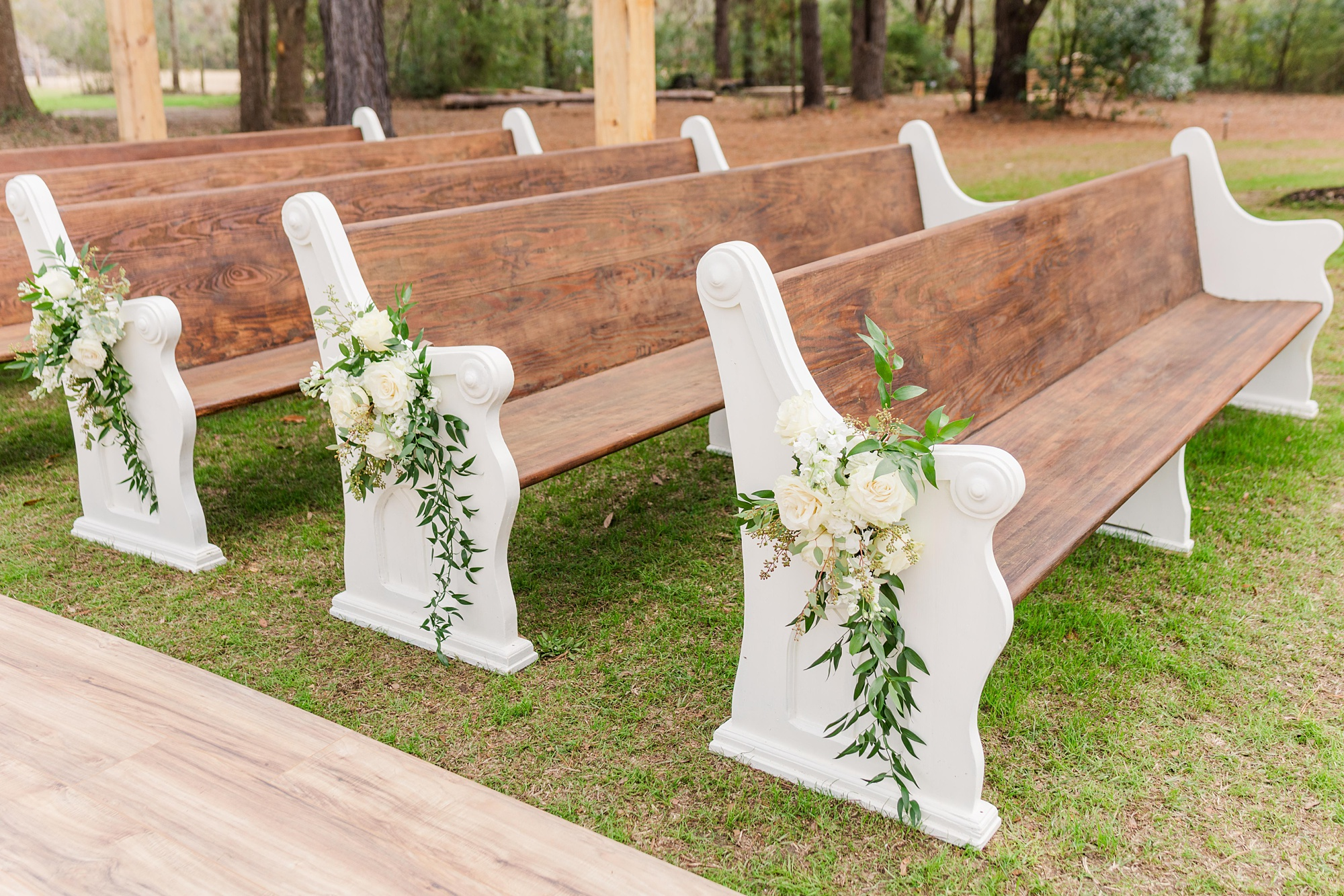 wooden pews with white flowers for wedding ceremony