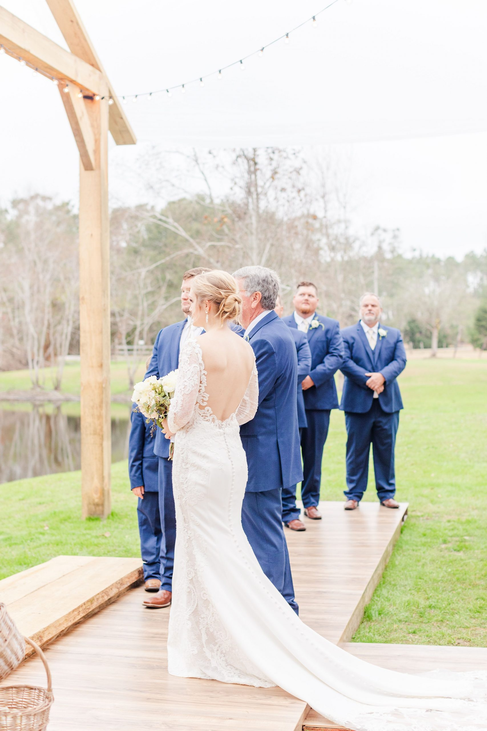 bride poses with father at ceremony