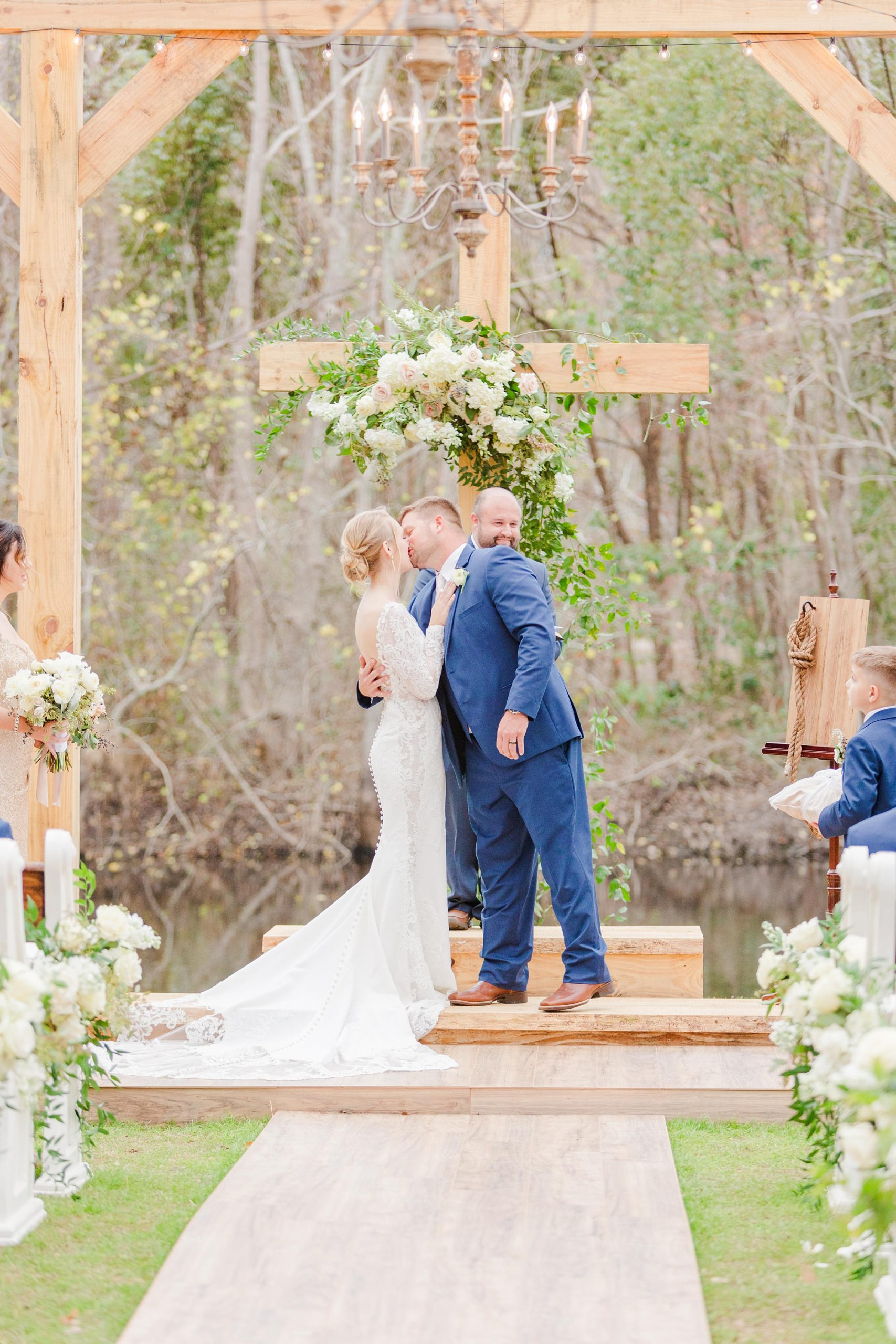 bride and groom kiss at wooden cross during ceremony