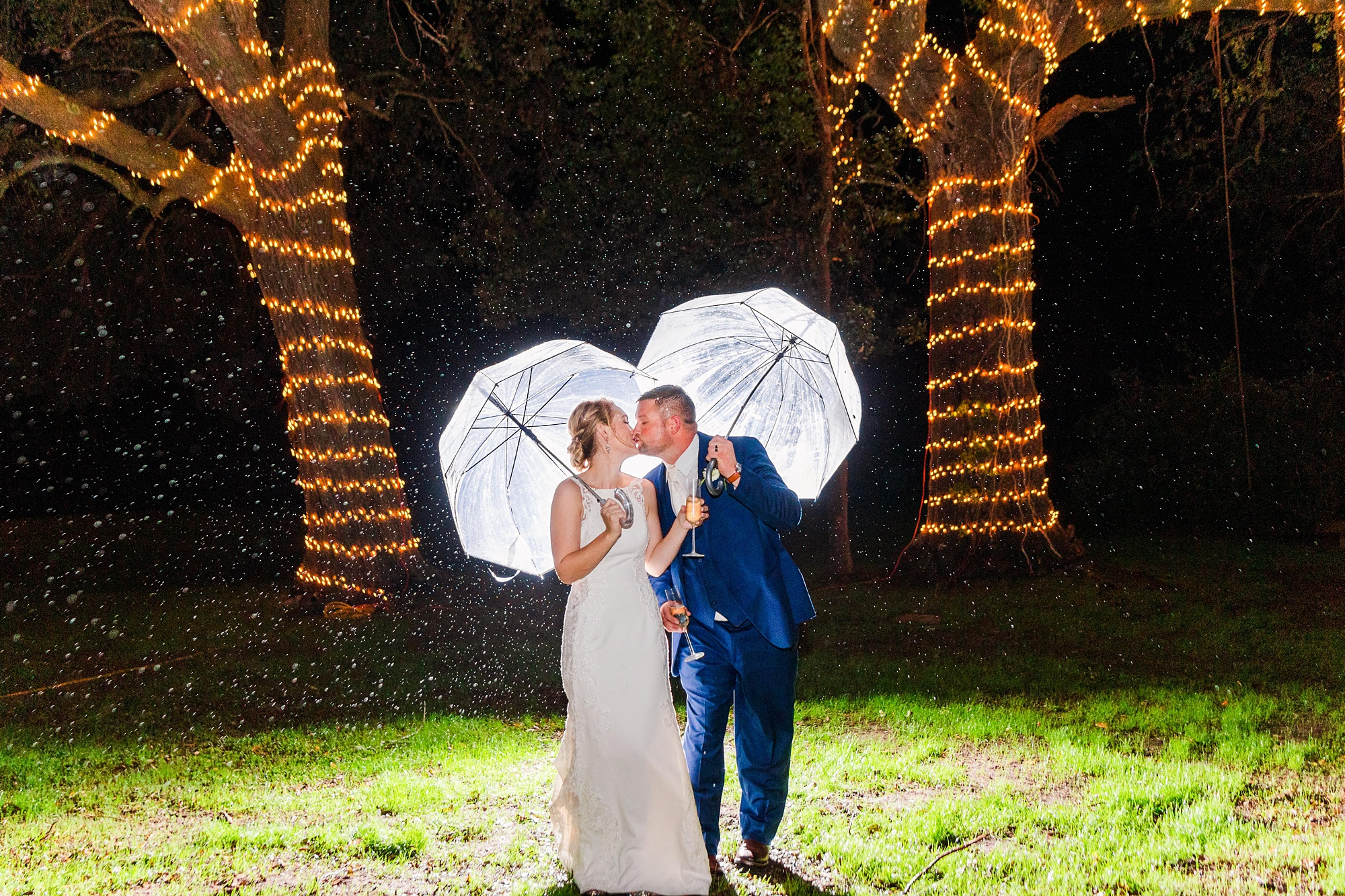 bride and groom kiss under umbrellas during rain storm