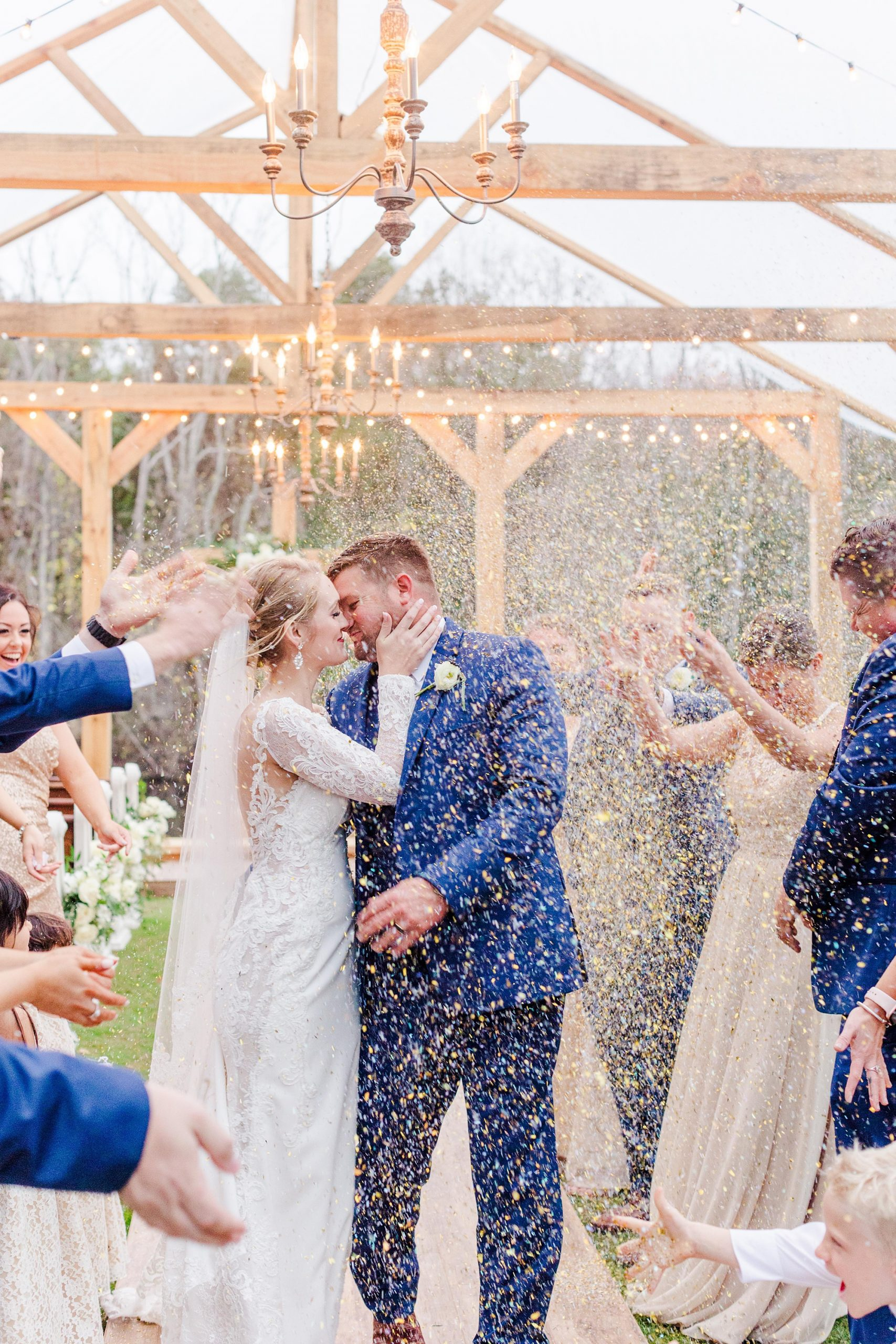 wedding party throws rice around bride and groom