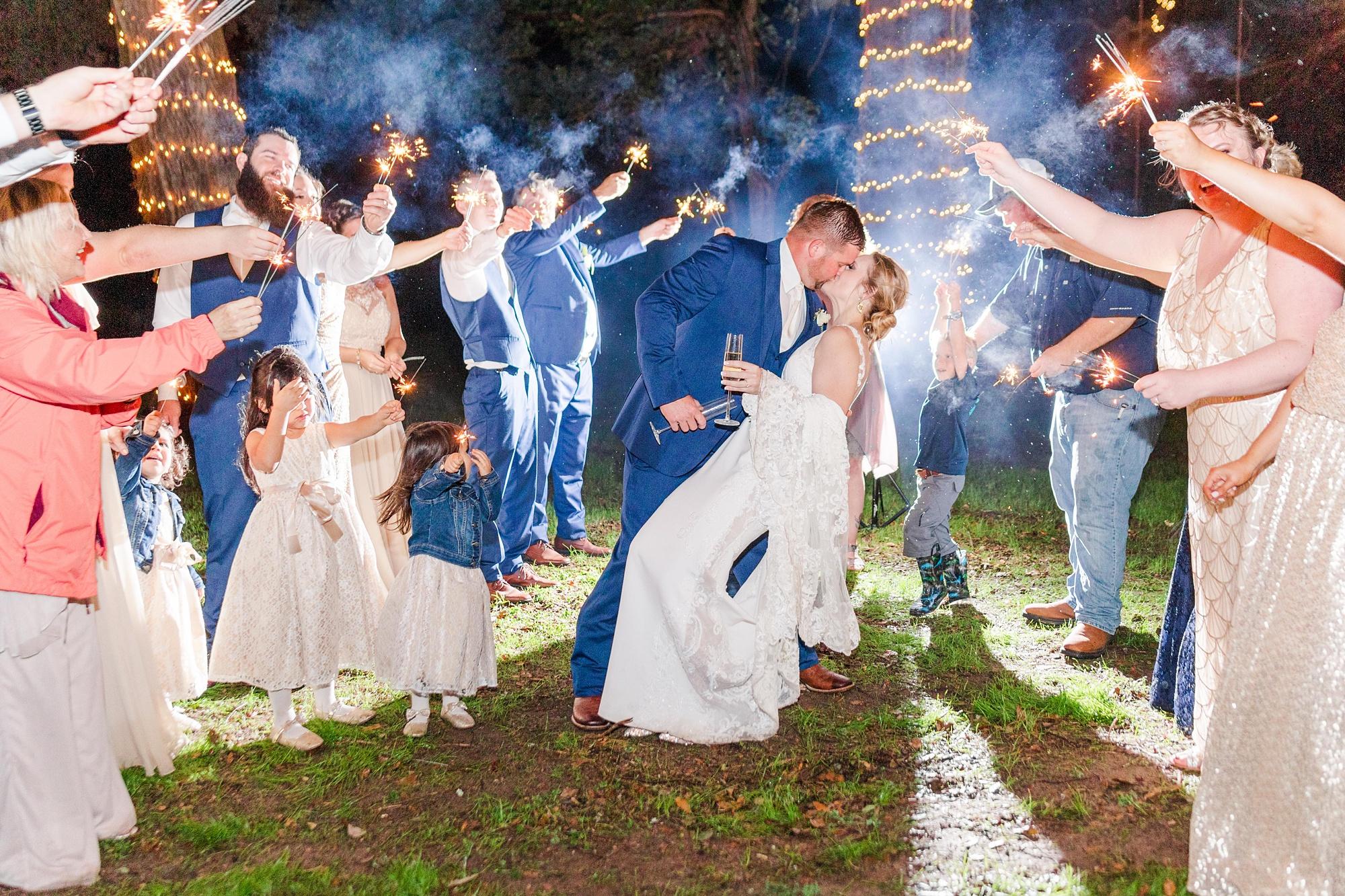 bride and groom kiss during sparkler exit in Magnolia Springs AL