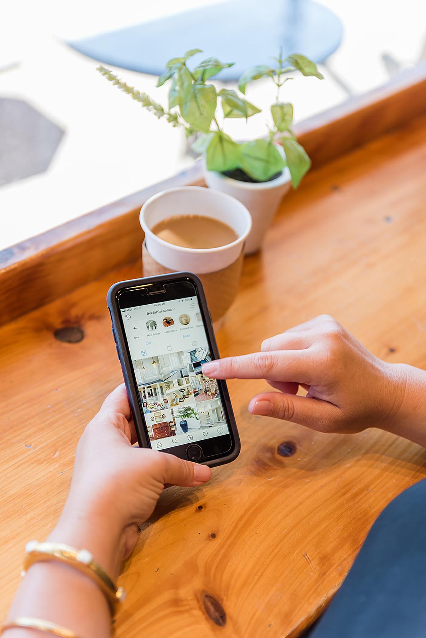woman scrolls on phone in coffee shop