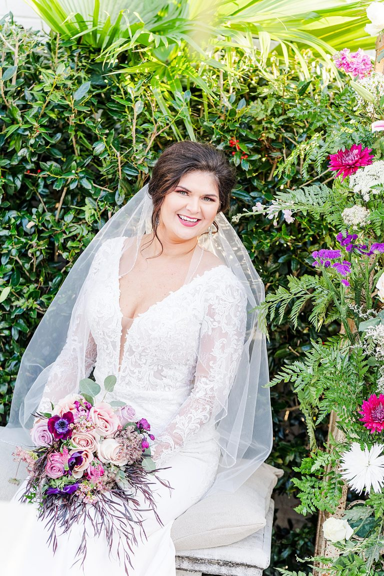 garden bridal portraits with bride holding bouquet of pink and purple flowers