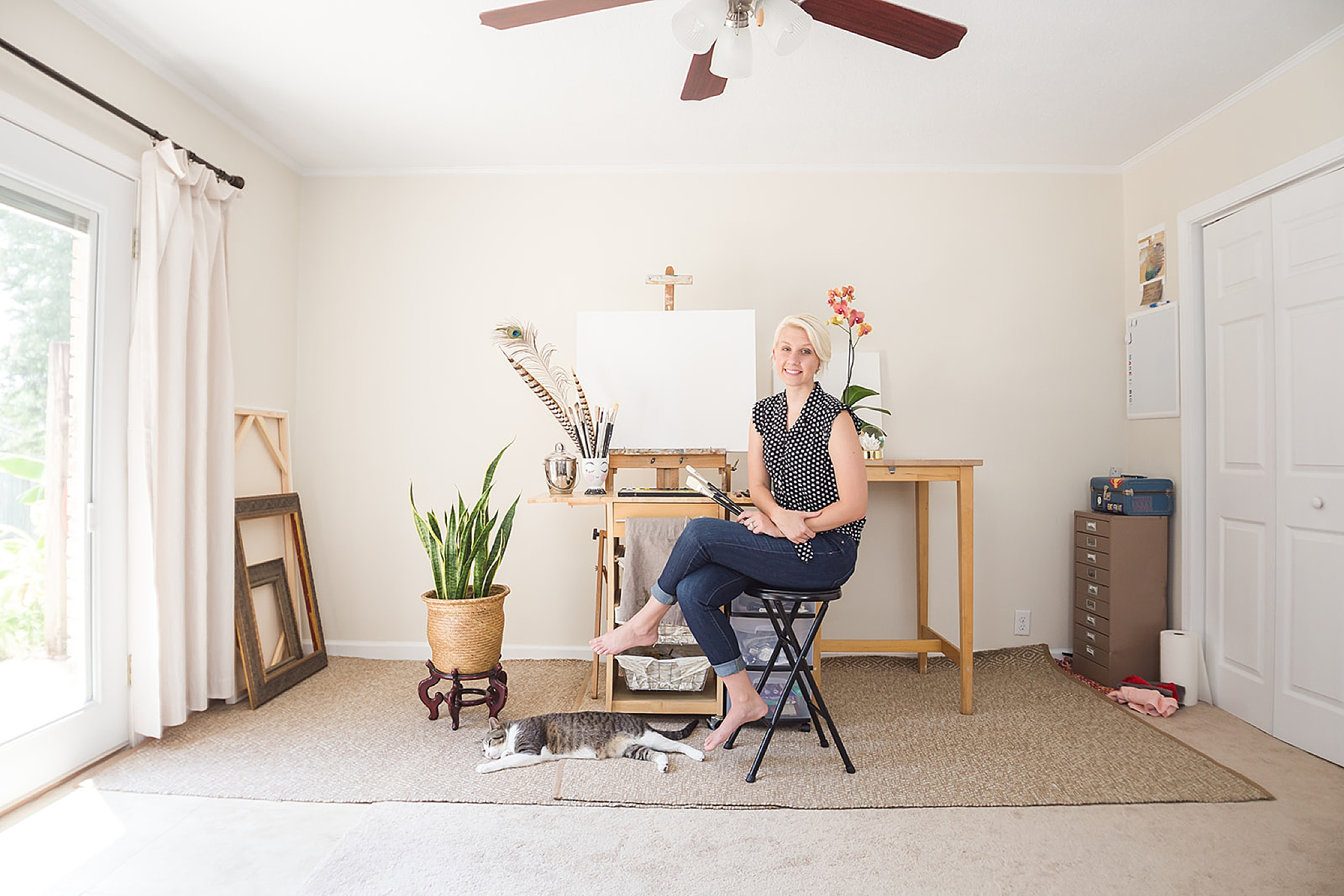 artist poses with cat in home studio during branding photos