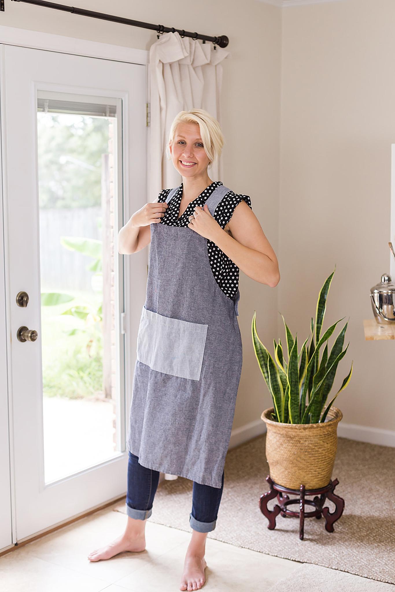 artist puts on apron in home studio