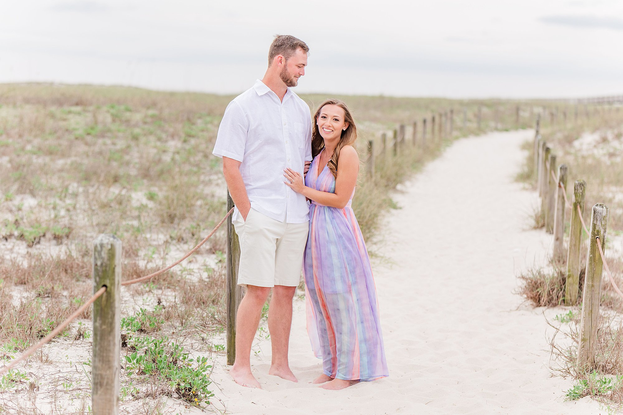 Groom looking at his bride at their engagement session in Orange Beach, Alabama